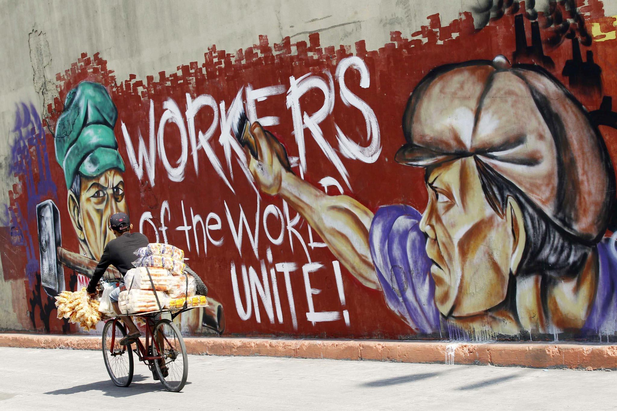 A man peddling food rides his bicycle past a graffiti along a street in Manila