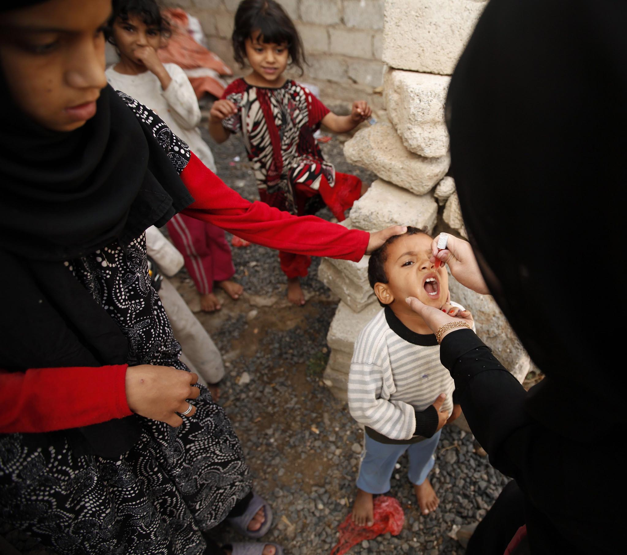 A health worker gives polio vaccine drops to a boy in an outskirt of the Yemeni capital Sanaa