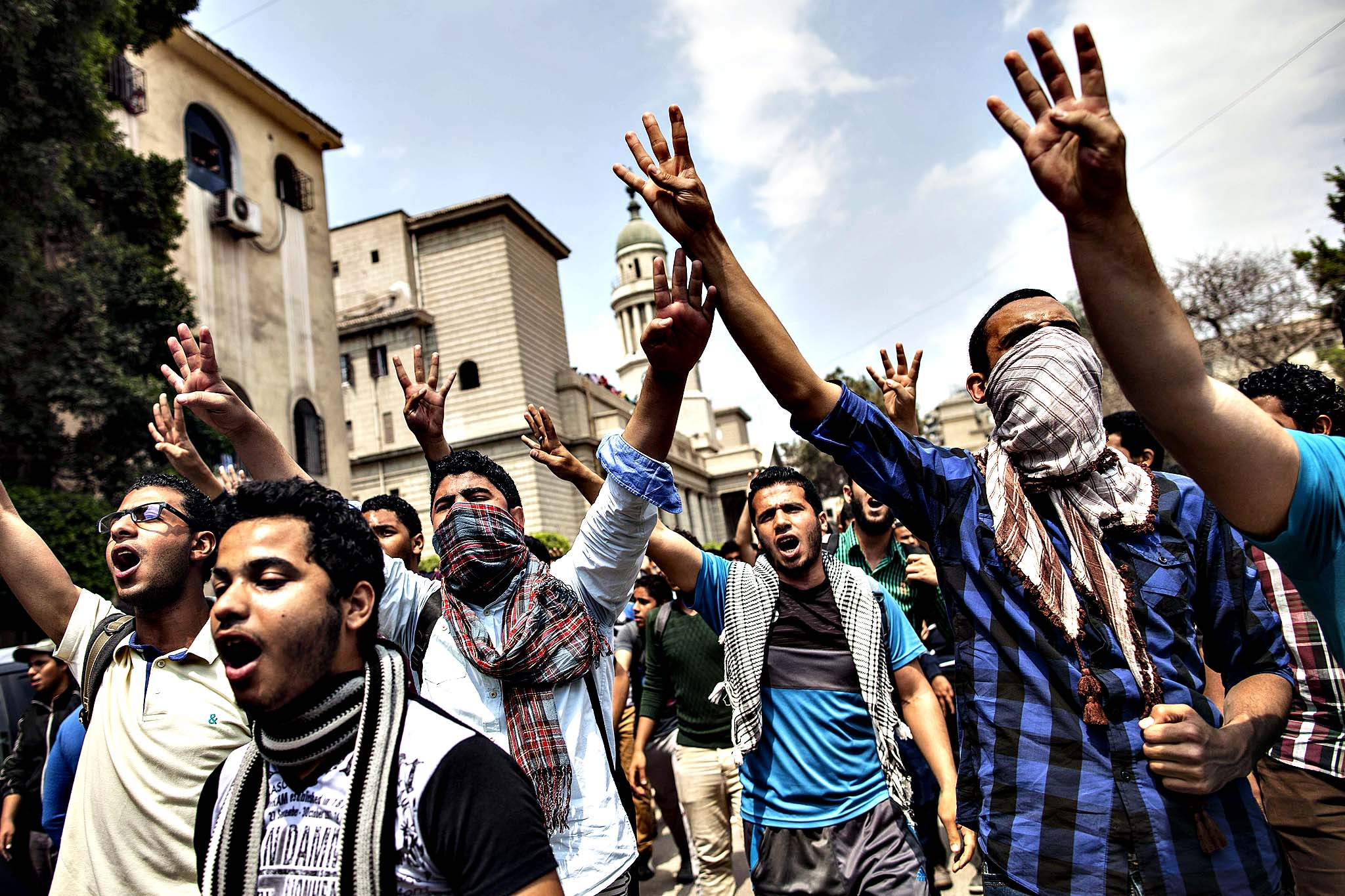 "Egyptian students, supporters of the Muslim Brotherhood and ousted Islamist president Mohamed Morsi,  flash the four finger symbol known as ""Rabaa"", meaning four in Arabic, which is associated with those killed in the crackdown on the Rabaa al-Adawiya protest camp in Cairo last year, as they demonstrate outside Cairo University, on April 9, 2014. An Egyptian appeals court rejected a request that new judges be appointed for two trials involving ousted Islamist president Mohamed Morsi, judicial officials said."