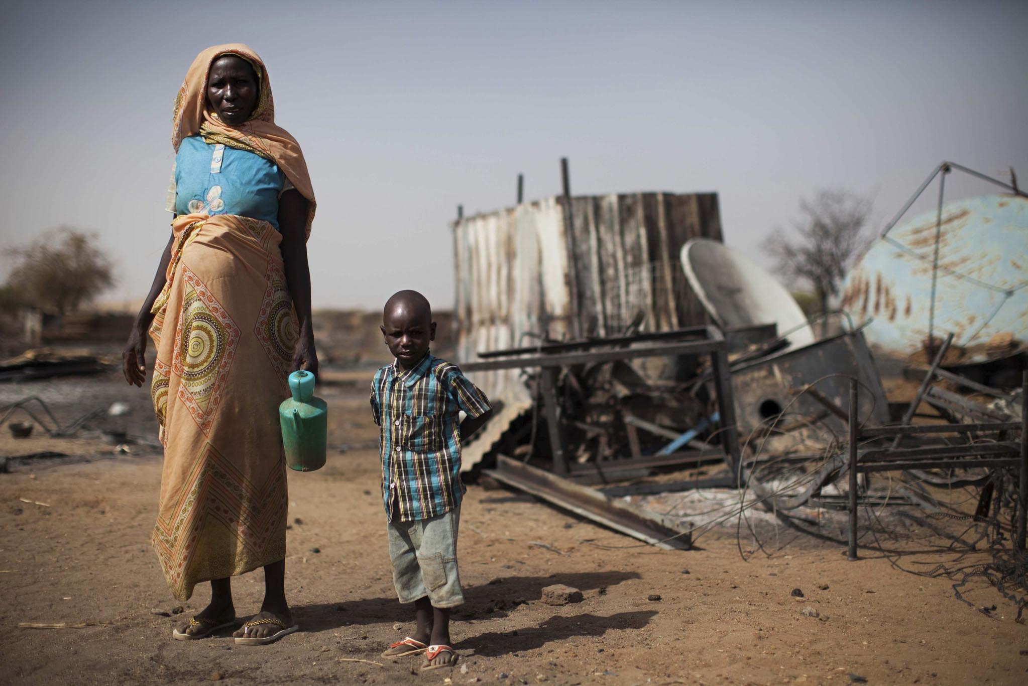 A displaced mother and her child inspect the remnants of their burnt house in Khor Abeche