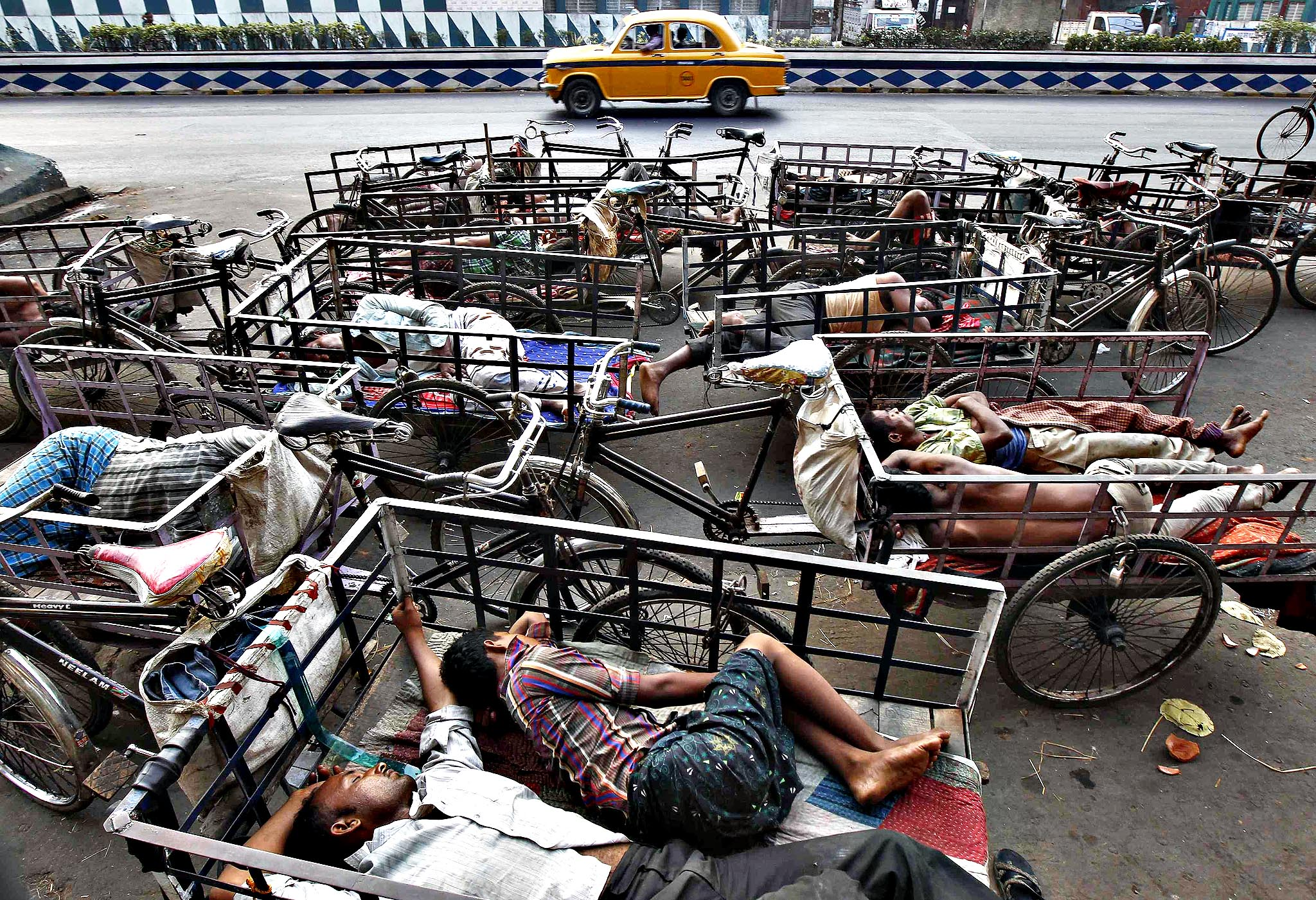 A yellow Ambassador taxi moves past cycle rickshaw pullers sleeping along a roadside in the early morning in Kolkata April 1, 2014.