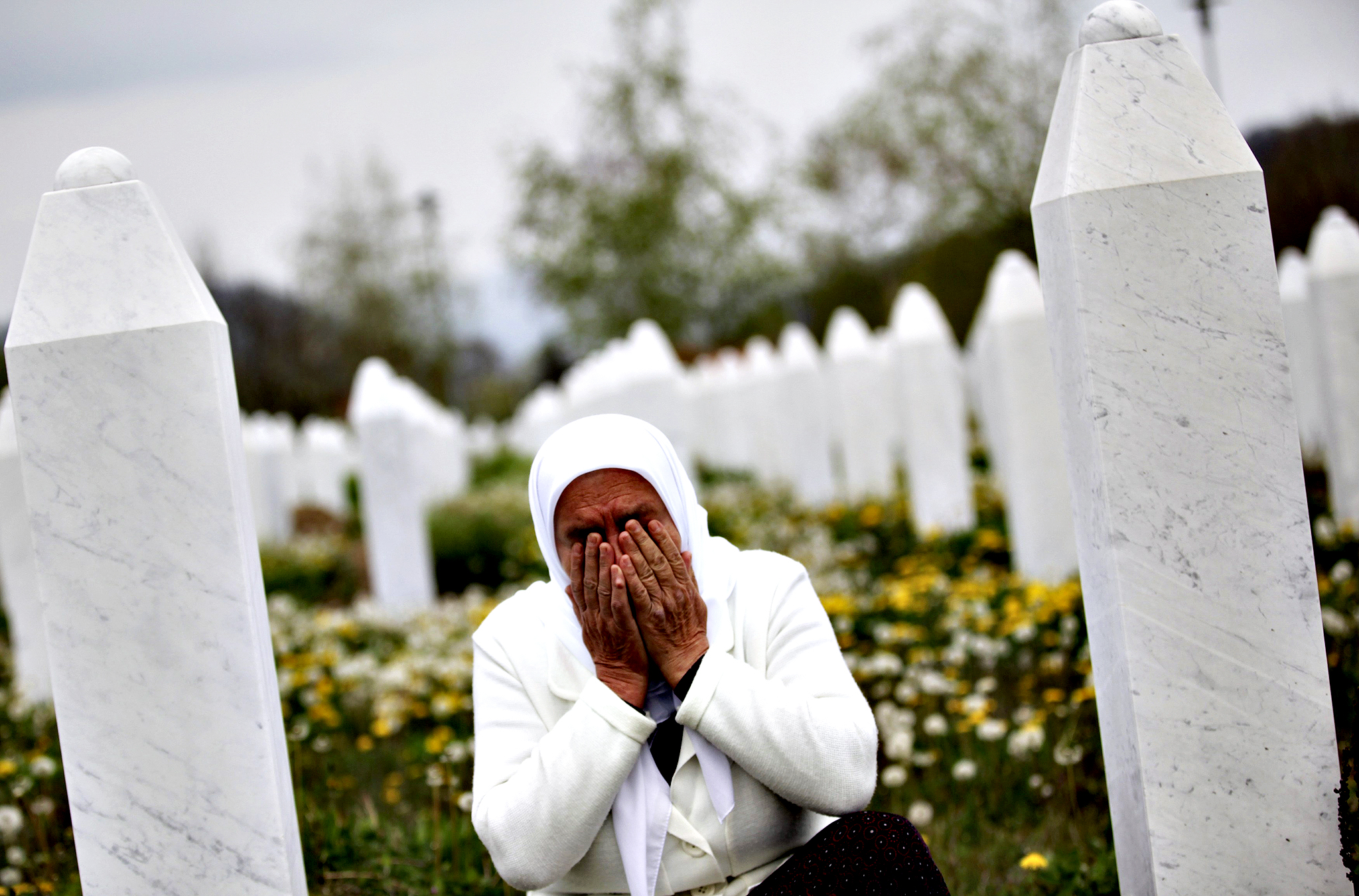 Mejra Dzogaz cries near the graves of her family members at the Memorial Center in Potocari April 7, 2014. Dzogaz lost her three sons, husband and father in the Srebrenica massacre. Survivors of the Srebrenica massacre are suing the Netherlands' government for failing to protect them from the rebel Serbs who killed some 8,000 men and boys in 1995. The case starting on Monday will determine the responsibility of the Dutch troops, under United Nations command, stationed in the eastern Bosnian town at the time of the killing.