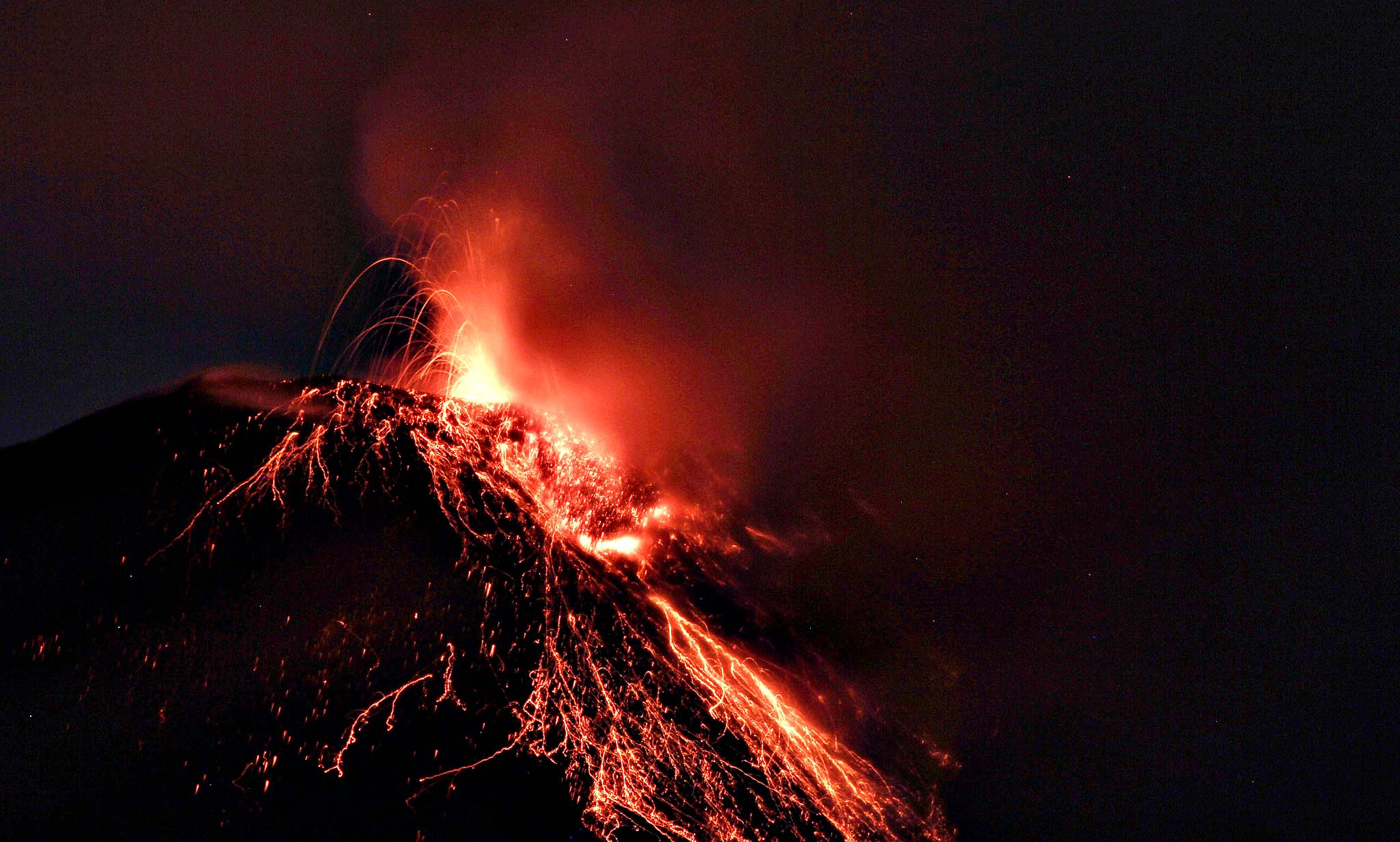 Lava spewed by the Tungurahua volcano can be seen from the city of Banos, Ecuador. An orange alert was issued by the volcanic activity of the Tungurahua