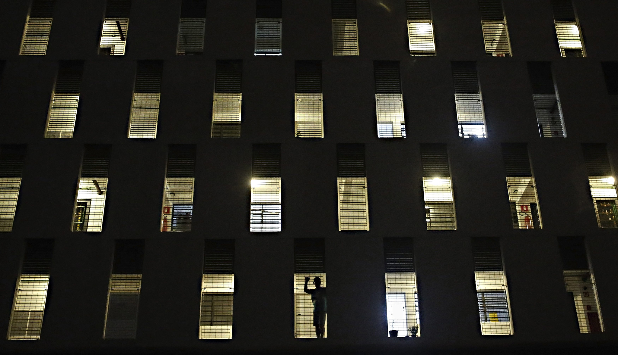 A man looks at members of Brazil's Homeless Workers' Movement (MTST) from his apartment during a protest against the World Cup in Sao Paulo. Brazilians opposed to the World Cup and the public funds spent on the construction of stadiums.
