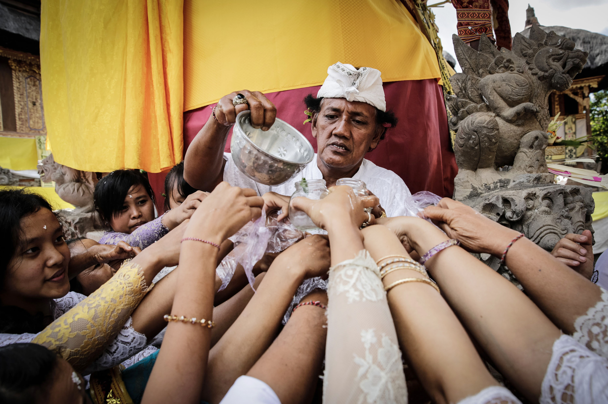 """Balinese Hindus celebrate Galungan Day...GIANYAR, BALI, INDONESIA - MAY 21:  A Balinese Hindus man pours holy water for belivers during they celebrate Galungan Day at a temple on May 21, 2014 in Gianyar, Bali, Indonesia. Galungan is an important feast for Balinese Hindus which is held every 210 days according to the Balinese calendar, to honor the creator of the universe and the spirits of the honored ancestors. The festival symbolize the victory of """"dharma"""", or truth, above """"adharma"""", or evil.  (Photo by Agung Parameswara/Getty Images)"""