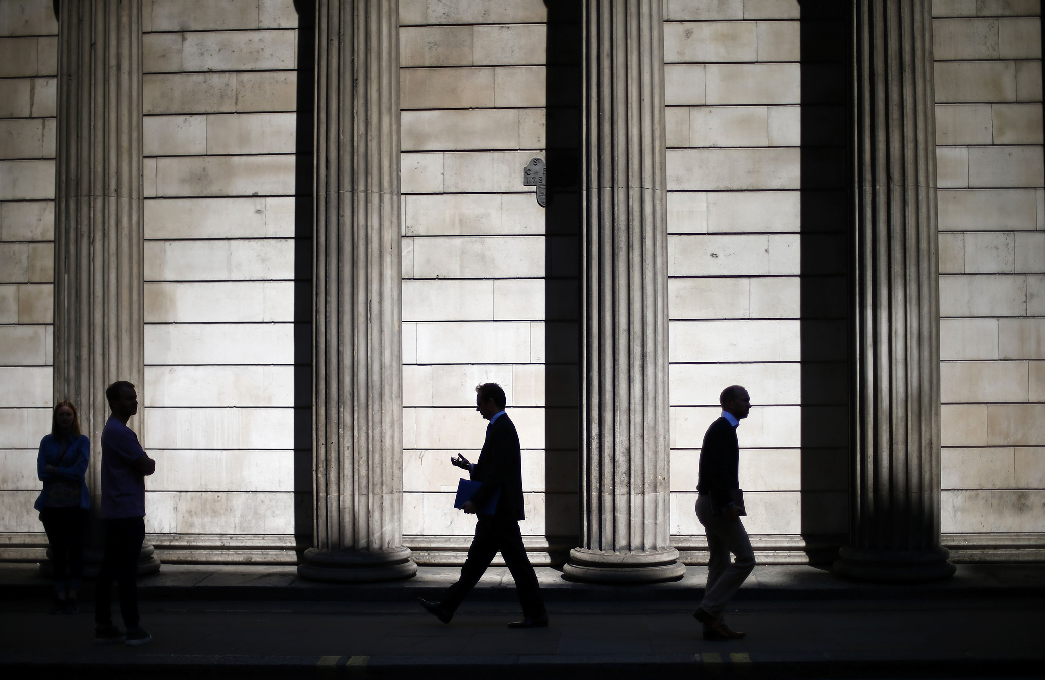 People are silhouetted as they walk past the columns of the Bank of England in the City of London...People are silhouetted on a sunny morning as they walk past the columns of the Bank of England in the City of London, May 19, 2014. Sterling eased on Monday, on growing talk the Bank of England will step in to cool the UK housing market, which would allow the central bank to keep interest rates lower for longer to sustain recovery elsewhere in the economy.