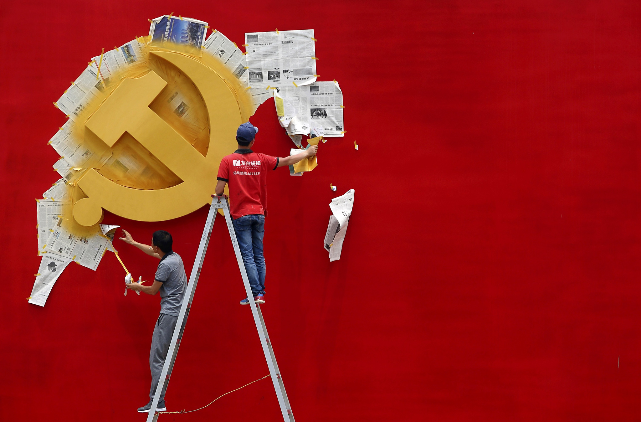 Workers peel papers off a wall as they re-paint the Chinese Communist Party flag on it at the Nanhu revolution memorial museum in Jiaxing...Workers peel papers off a wall as they re-paint the Chinese Communist Party flag on it at the Nanhu revolution memorial museum in Jiaxing, Zhejiang province May 21, 2014. REUTERS/Chance Chan (CHINA - Tags: POLITICS SOCIETY)