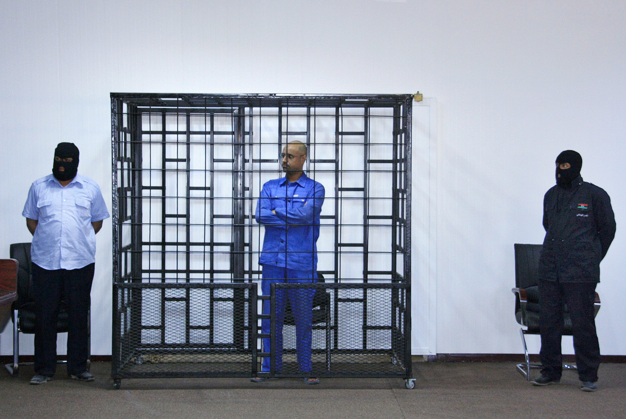 Saif al-Islam Gaddafi attends a hearing behind bars in a courtroom in Zintan...Saif al-Islam Gaddafi, son of late Libyan leader Muammar Gaddafi, attends a hearing behind bars in a courtroom in Zintan May 15, 2014. REUTERS/Stringer