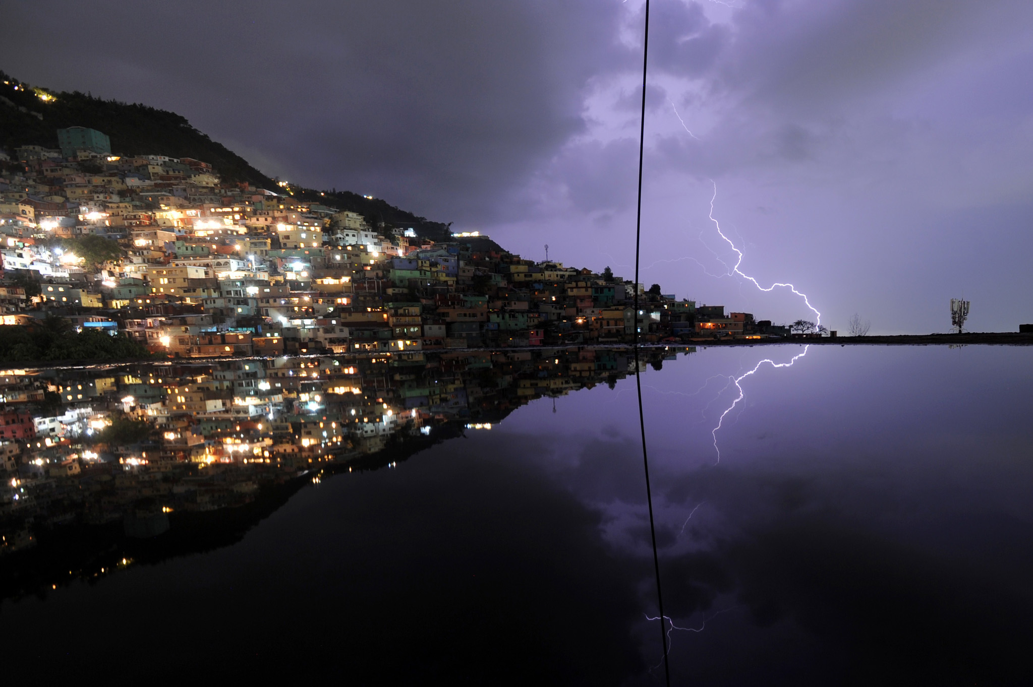TOPSHOTS A long exposure shows lightning...TOPSHOTS A long exposure shows lightning in the sky with reflection in the water on the floor of a building under construction during an evening thunderstorm on May 19, 2014 in the Haitian capital Port-au-Prince.   AFP PHOTO/Hector RETAMALHECTOR RETAMAL/AFP/Getty Images