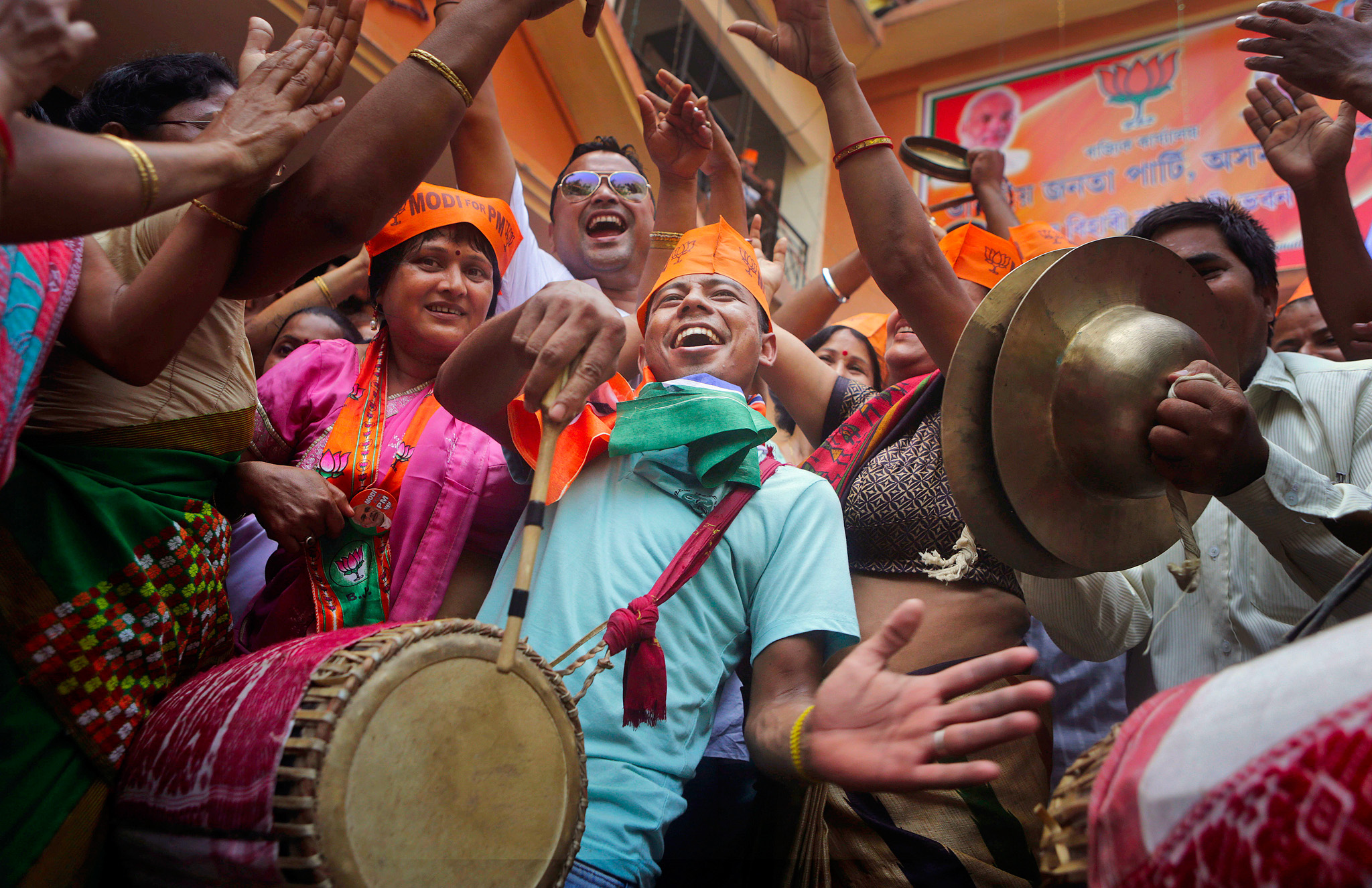 Bharatiya Janata Party (BJP) supporters celebrate the party's winning preliminary result outside their office in Gauhati, India, Friday, May 16, 2014. India's opposition leader Narendra Modi and his party won national elections in a landslide Friday, preliminary results showed, driving the long-dominant Congress party out of power in the most commanding victory India has seen in more than a quarter century. (AP Photo/Anupam Nath)
