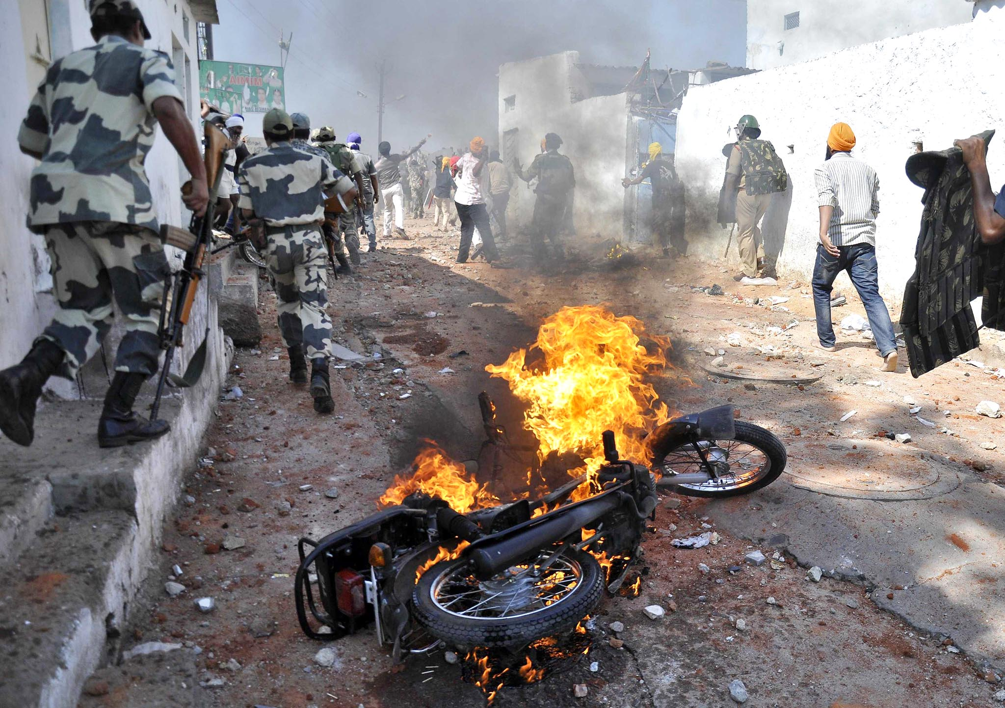 A motorcycle set on fire by a mob burns during clashes between two communities on the outskirts of Hyderabad