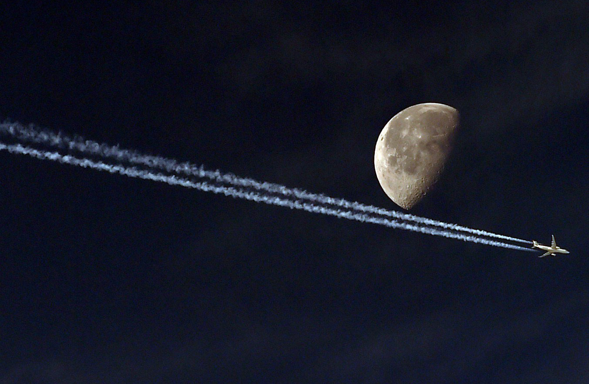 TOPSHOTS A jetliner leave a vapour trail...TOPSHOTS A jetliner leave a vapour trail as it passes in front of the moon on May 20, 2014, taken from the Algerian capital Algiers. AFP PHOTO/FAROUK BATICHEFAROUK BATICHE/AFP/Getty Images