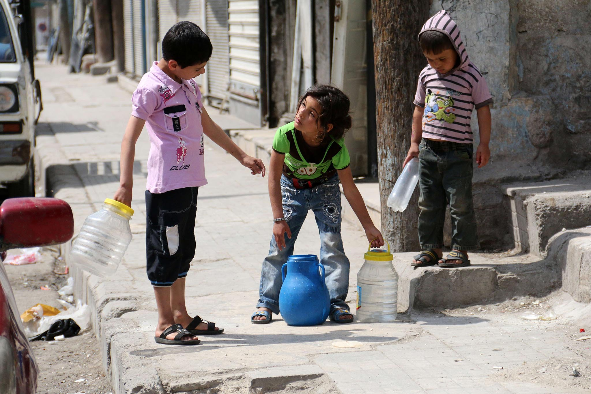 Children carry buckets of water in a rebel-held area in Aleppo