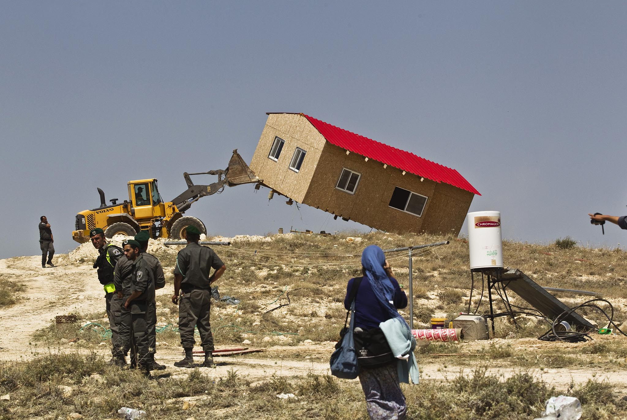 Israeli border policemen stand near a bulldozer as it demolishes a temporary structure in the West Bank Jewish settler outpost of Maale Rehavam