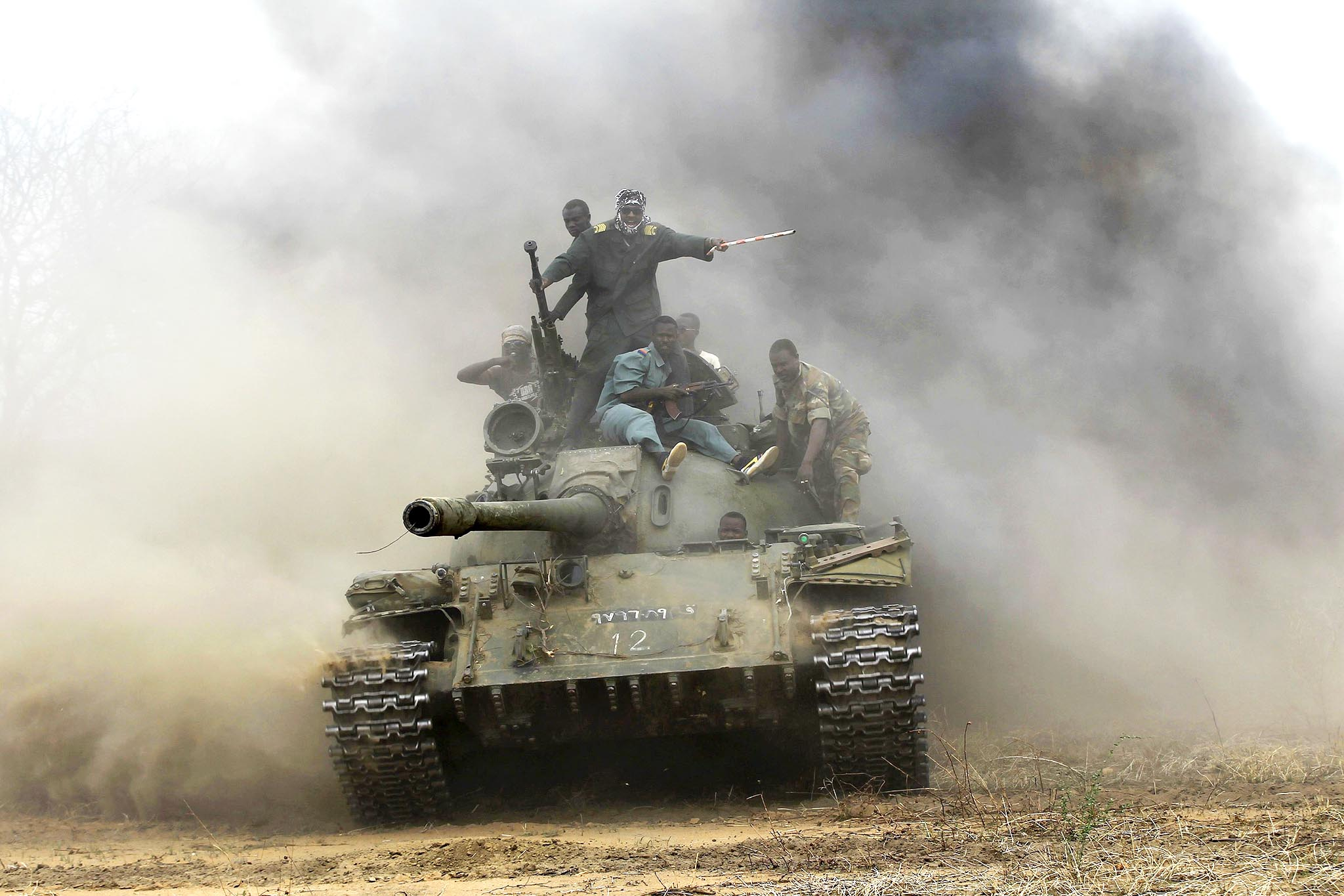 Sudanese Armed Forces and Rapid Support Forces personnel ride on a tank after recapturing the Daldako area