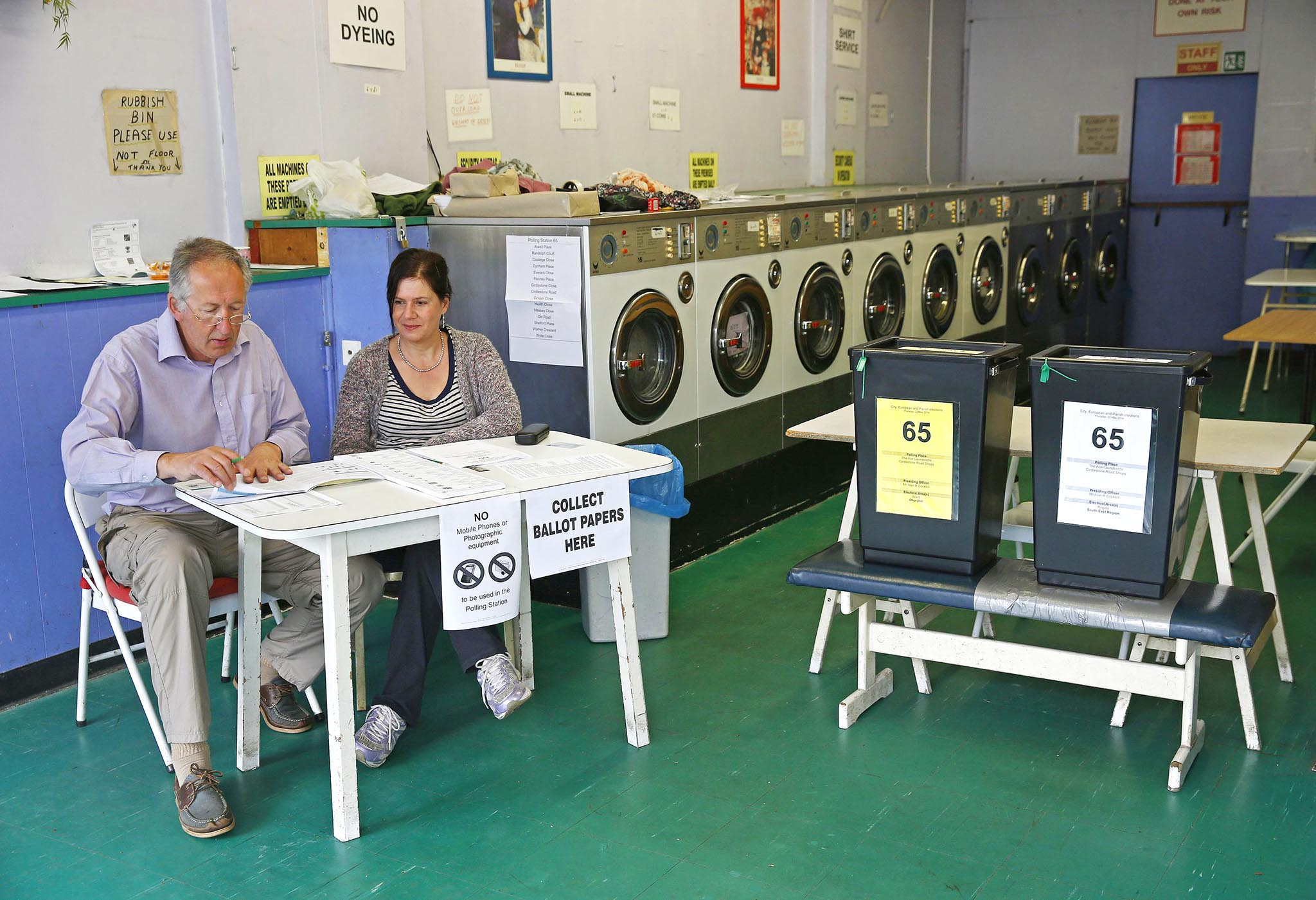 Poll clerks are seen in a launderette being used as a polling station in Oxford