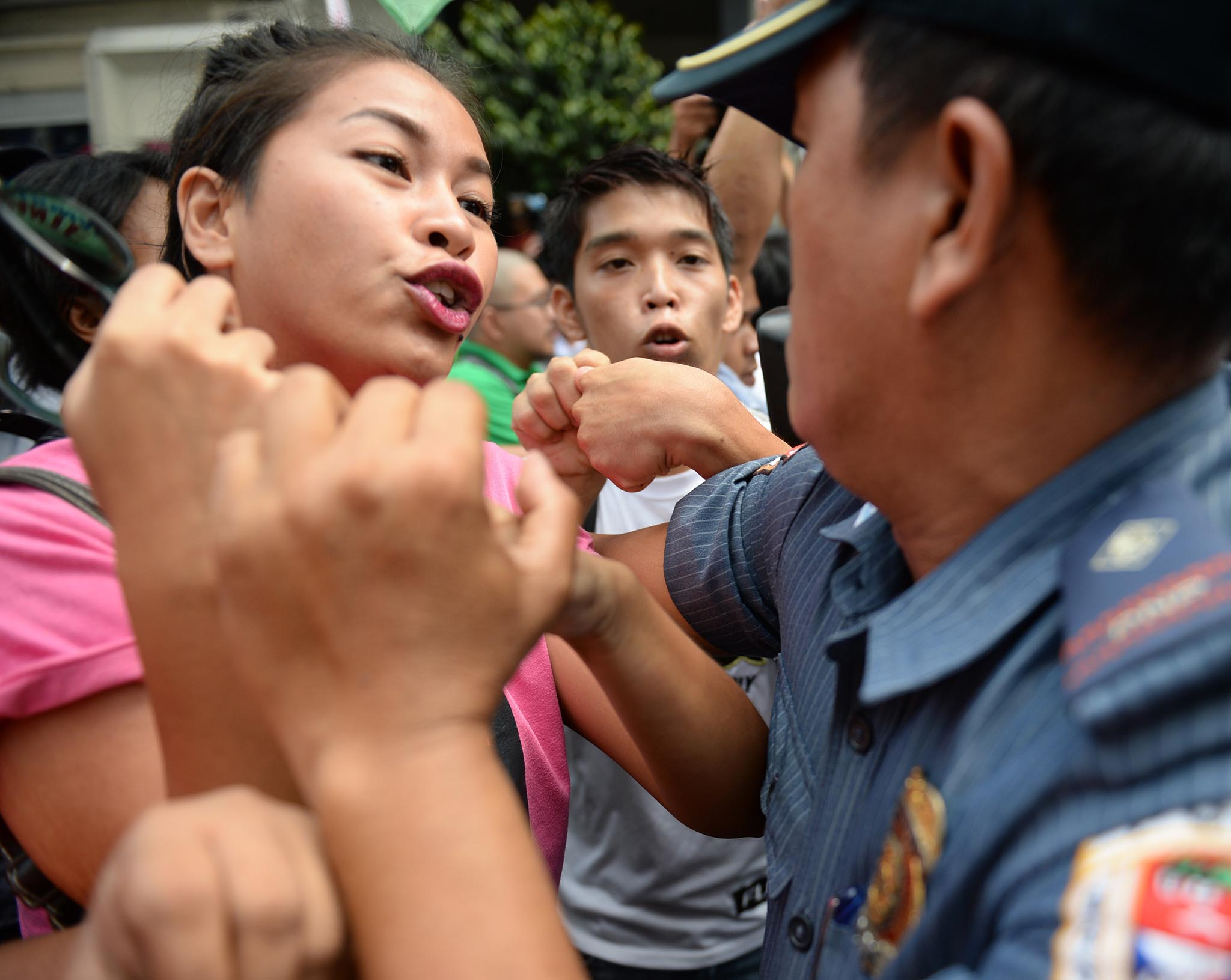 A Philippine policeman attempts to arrest a demonstrator