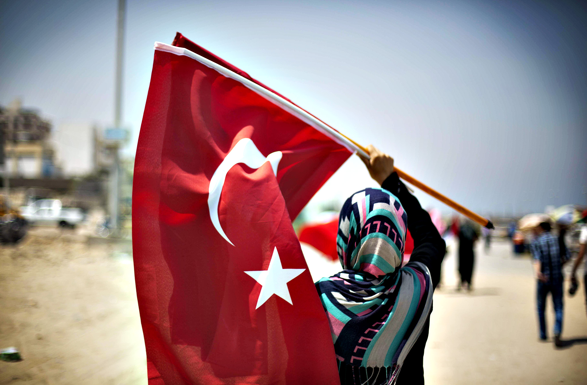 A Palestinian girl holds Turkish flags in Gaza Port on May 29, 2014 during the visit of Turkish ambassador in Palestine Mustafa Sarnic (unseen) to lay flowers at the memorial of martyrs from the Turkish ship Mavi Marmara, that was part of a flotilla trying to break the Gaza blockade, who were killed when Israeli naval commandos seized the ship in May 2010.