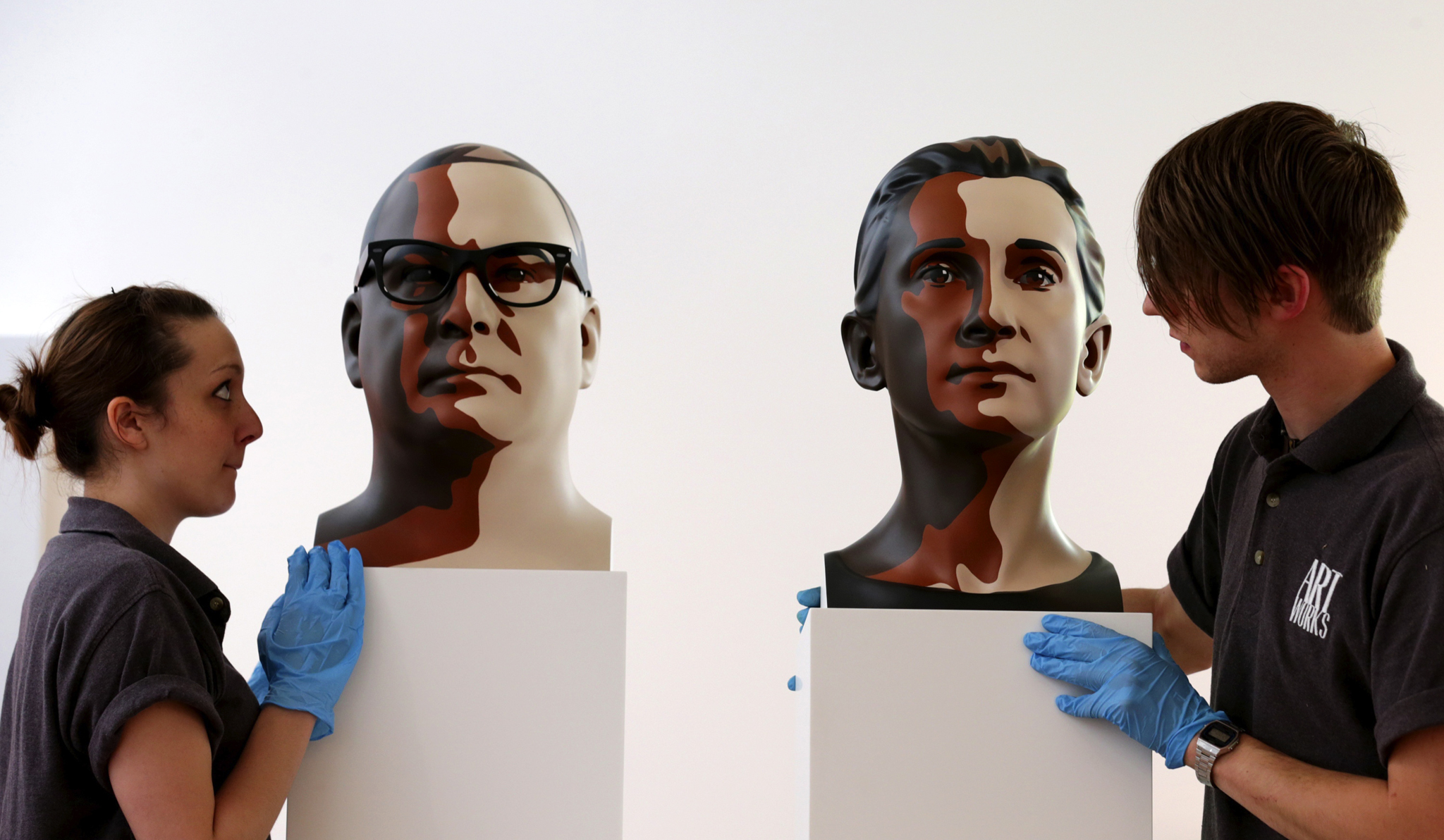 Artist Julian Opie Exhibition Opens In Bath...BATH, ENGLAND - MAY 15:  Art technicians Rachel Falber and Sam Roberts from Art Works position two three-dimensional sculptures, 'Reed 1' and 'Delphine 2' by the artist Julian Opie onto plinths inside the Holburne Museum on May 15, 2014 in Bath, England. Considered to be one of the UK's most important and successful contemporary artists, the exhibition, 'Julian Opie: Collected Works', opens next Wednesday and runs until September 14. It will be the artists first one person exhibition for over ten years and will bring together his own works, including several previously unseen works, with pieces from his private collection.  (Photo by Matt Cardy/Getty Images)