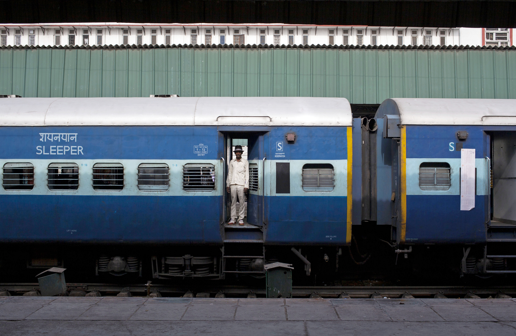 An Indian man stands at the doorway of a train at a railway station in New Delhi, India, Wednesday, May 14, 2014.  Indian railway network is one of the world's largest, with some 14 million passengers daily and some 64,000 kilometers (40,000 miles) of railway track cut through some of the most densely populated cities. (AP Photo/Tsering Topgyal)