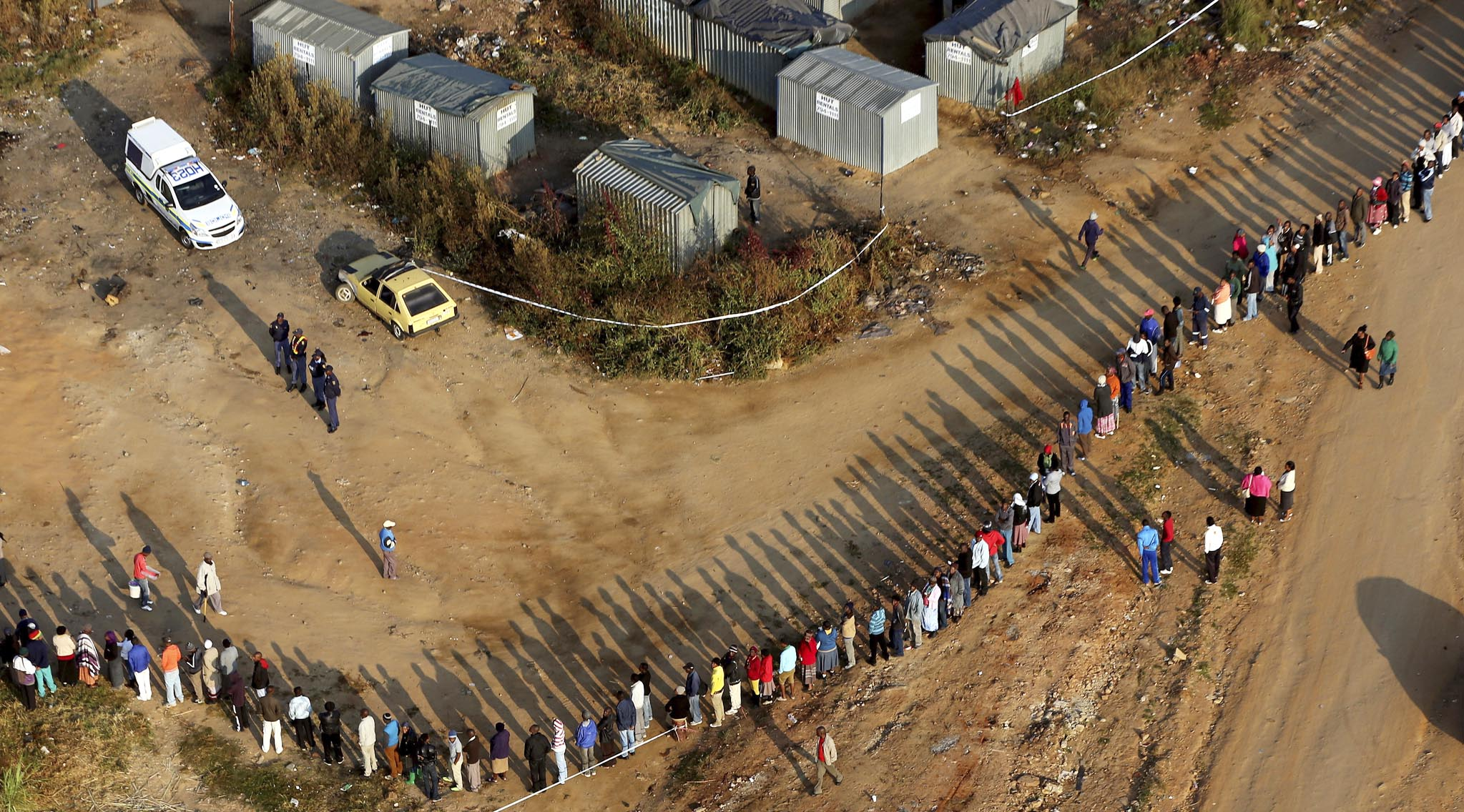 South Africans queue to vote at a polling station in Zandspruit, west of Johannesburg, South Africa, Wednesday, May 7, 2014. South Africans voted Wednesday in elections that are expected to see the ruling African National Congress return to power despite a vigorous challenge from opposition parties seeking to capitalize on discontent with corruption and economic inequality. (AP Photo/Themba Hadebe)