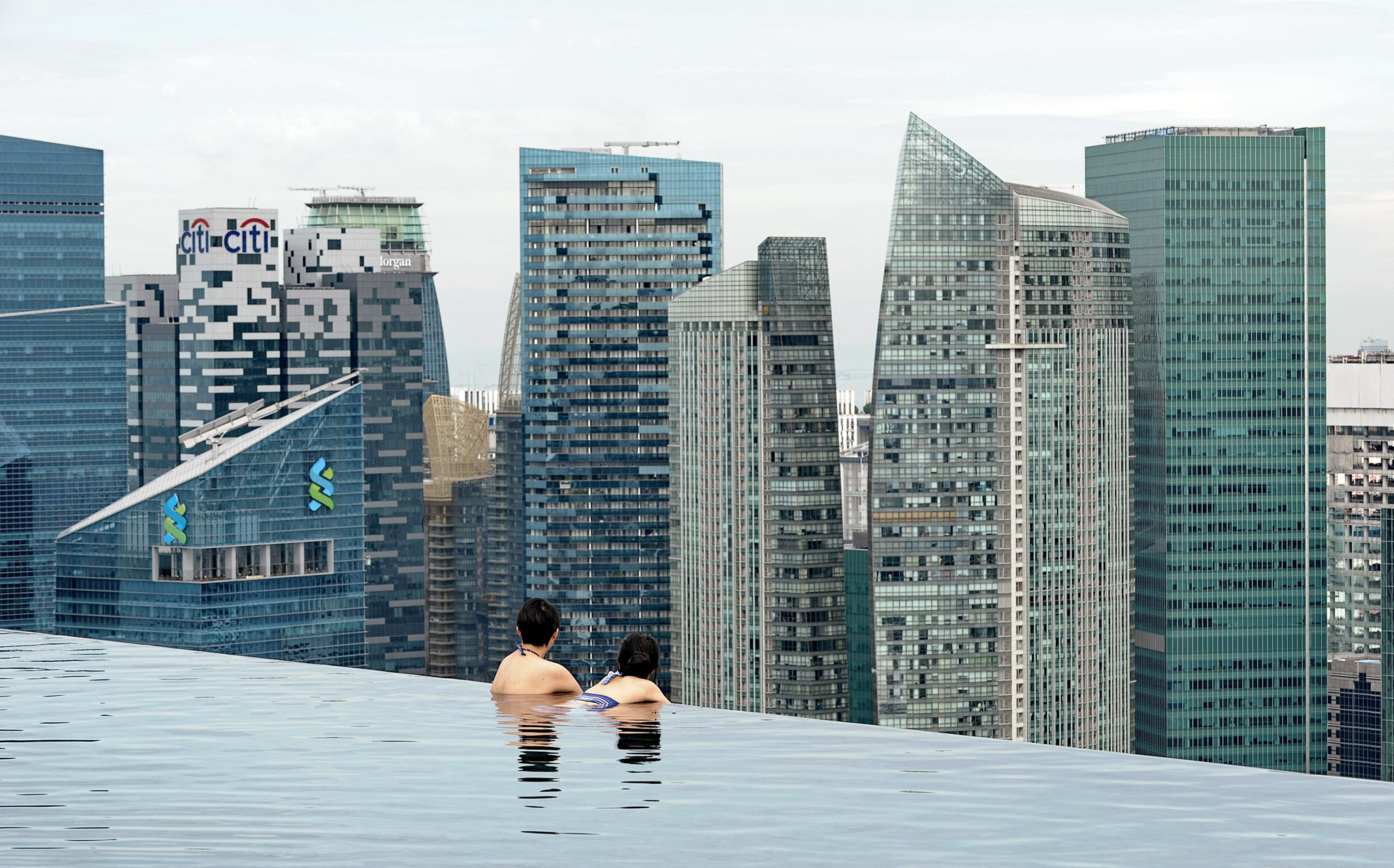 Visitors look at a view of the city skyl...Visitors look at a view of the city skyline from the rooftop pool of the Marina Bay Sands resort hotel in Singapore on May 20, 2014. Singapore's trade-reliant economy expanded a seasonally adjusted 2.3 percent quarter-on-quarter the trade ministry said May 20. AFP PHOTO/ROSLAN RAHMANROSLAN RAHMAN/AFP/Getty Images