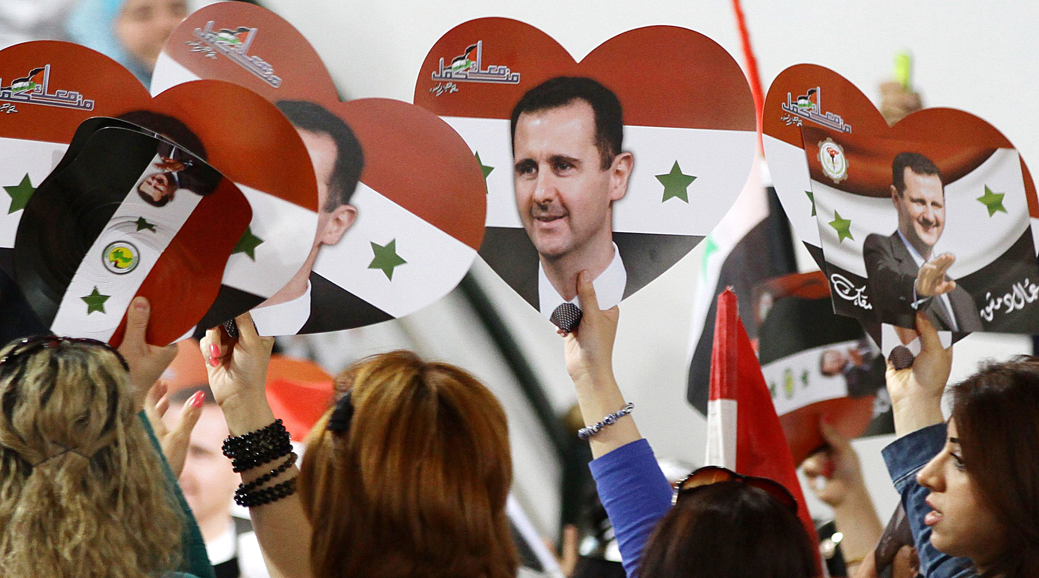 Syrians wave flags and placards bearing ...Syrians wave flags and placards bearing portraits President Bashar al-Assad during a meeting gathering workers to support his candidacy in upcoming presidential elections on May 13, 2014 in the capital Damscus. The campaign for Syria's elections that started this week, has become a tribute to incumbent Bashar al-Assad, and in the streets of Damascus, residents have little doubt who will win the June poll. AFP PHOTO/ LOUAI BESHARALOUAI BESHARA/AFP/Getty Images