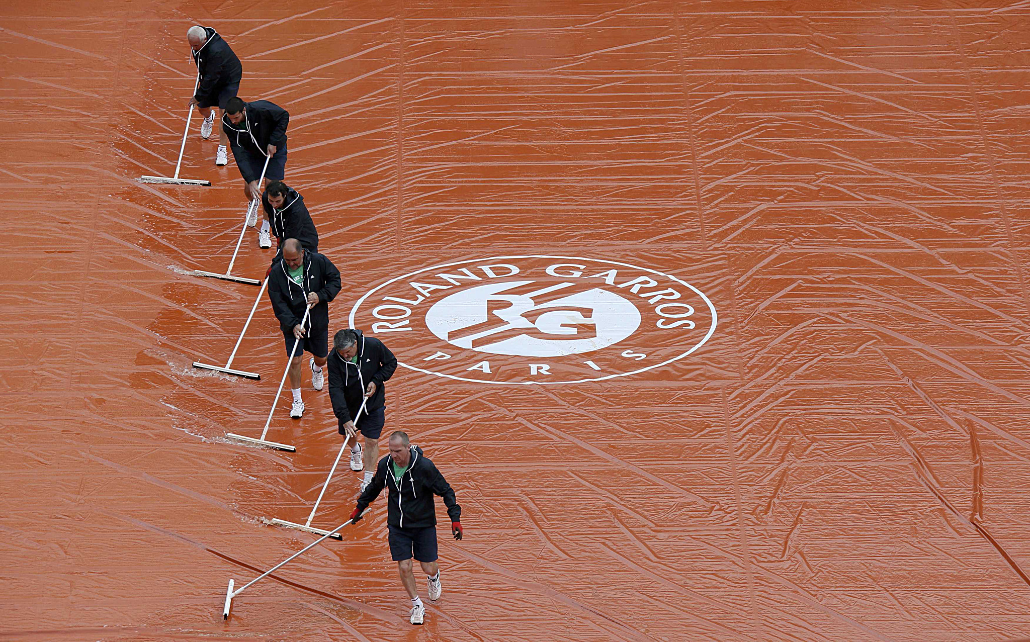 Workers sweep water off a tarp as rain interrupts a men's singles match between Djokovic of Serbia and Sousa of Portugal at the French Open tennis tournament at the Roland Garros stadium in Paris...Workers sweep water off a tarp as rain interrupts a men's singles match between Novak Djokovic of Serbia and Joao Sousa of Portugal at the French Open tennis tournament at the Roland Garros stadium in Paris May 26, 2014.     REUTERS/Gonzalo Fuentes