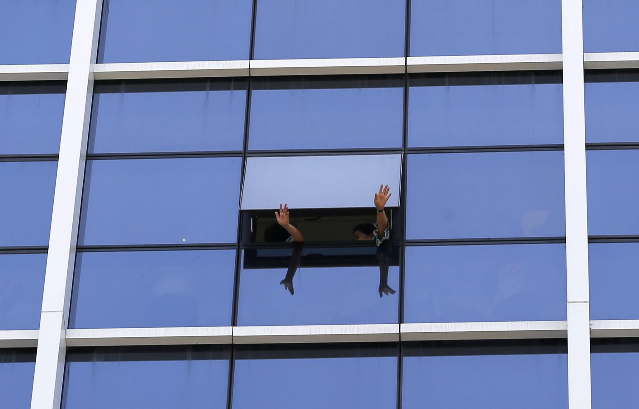 Anti-government protests in Bangkok...epa04202242 Thai office workers wave to cheer anti-government protesters from the window of a building during a street rally in Bangkok, Thailand, 12 May 2014. Anti-government protesters began moving their rally site in central Bangkok to the area surrounding parliament hoping to pressure the Senate to appoint an interim government to institute reforms before new elections while key Thai institutions are resisting opposition demands to install an appointed government to make political reforms, reports said.  EPA/RUNGROJ YONGRIT