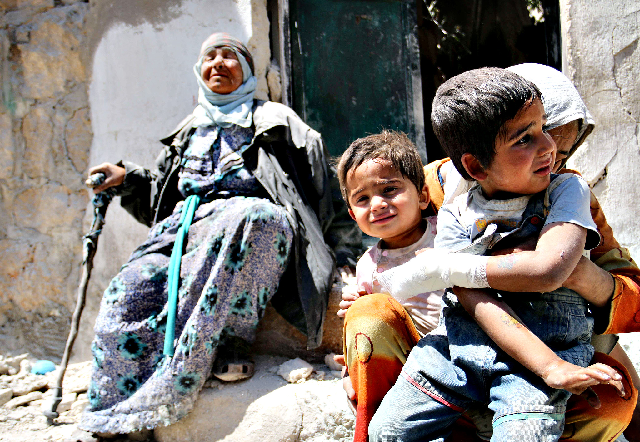 A Syrian woman comforts her children after their house in the Sahour nieghbourhood of the northern Syrian city of Aleppo was bombed on May 14, 2014. Once home to some 2.5 million residents and considered Syria's economic powerhouse, Aleppo has been divided between government and opposition control since shortly after fighting there began in mid-2012.