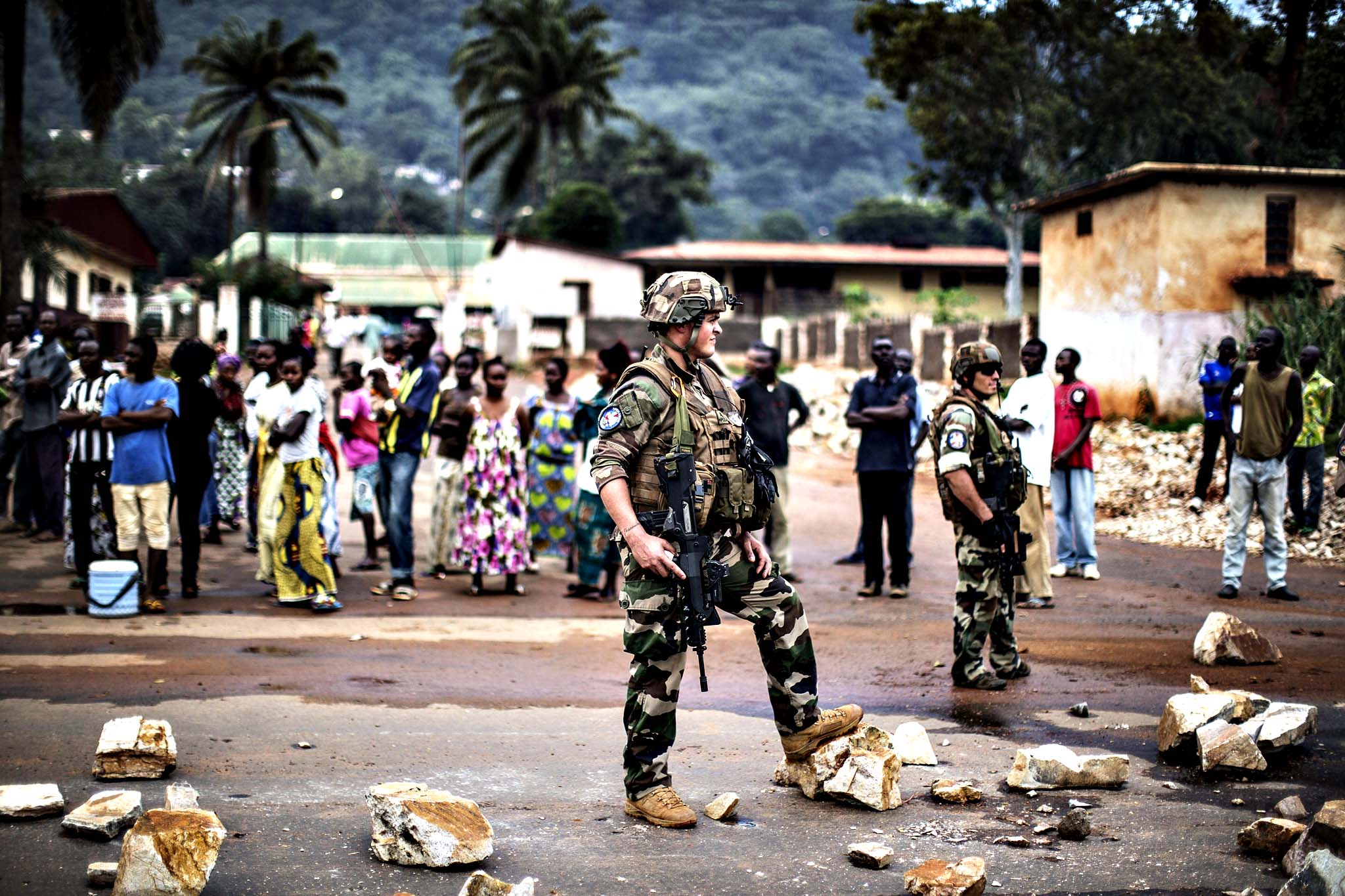 "French soldiers of the Sangaris contingent patrol the site of a barricade in central Bangui on May 30, 2014.  Security forces fired warning shots as protesters in Bangui demanded the resignation of the interim government and the removal of foreign troops from Central African Republic on Friday, a military source said. Central Africa's interim president Friday dubbed as a ""terrorist act"" this week's attack on a church in the capital Bangui that killed 17 people and led to 27 others being abducted on May 28."
