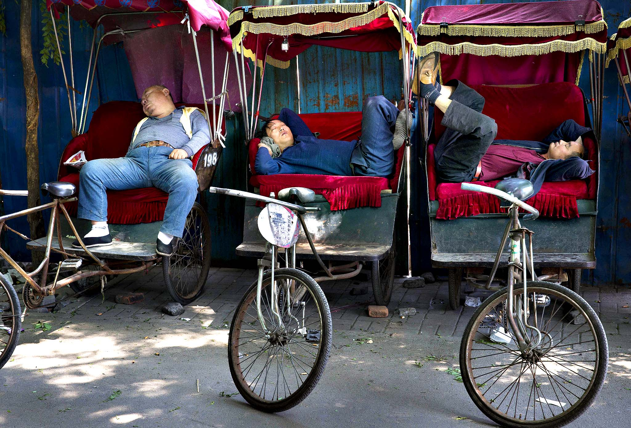 Chinese trishaw drivers take nap while waiting for customers at a hutong alley near the drum tower, a tourist spot in Beijing, China Wednesday, May 7, 2014.