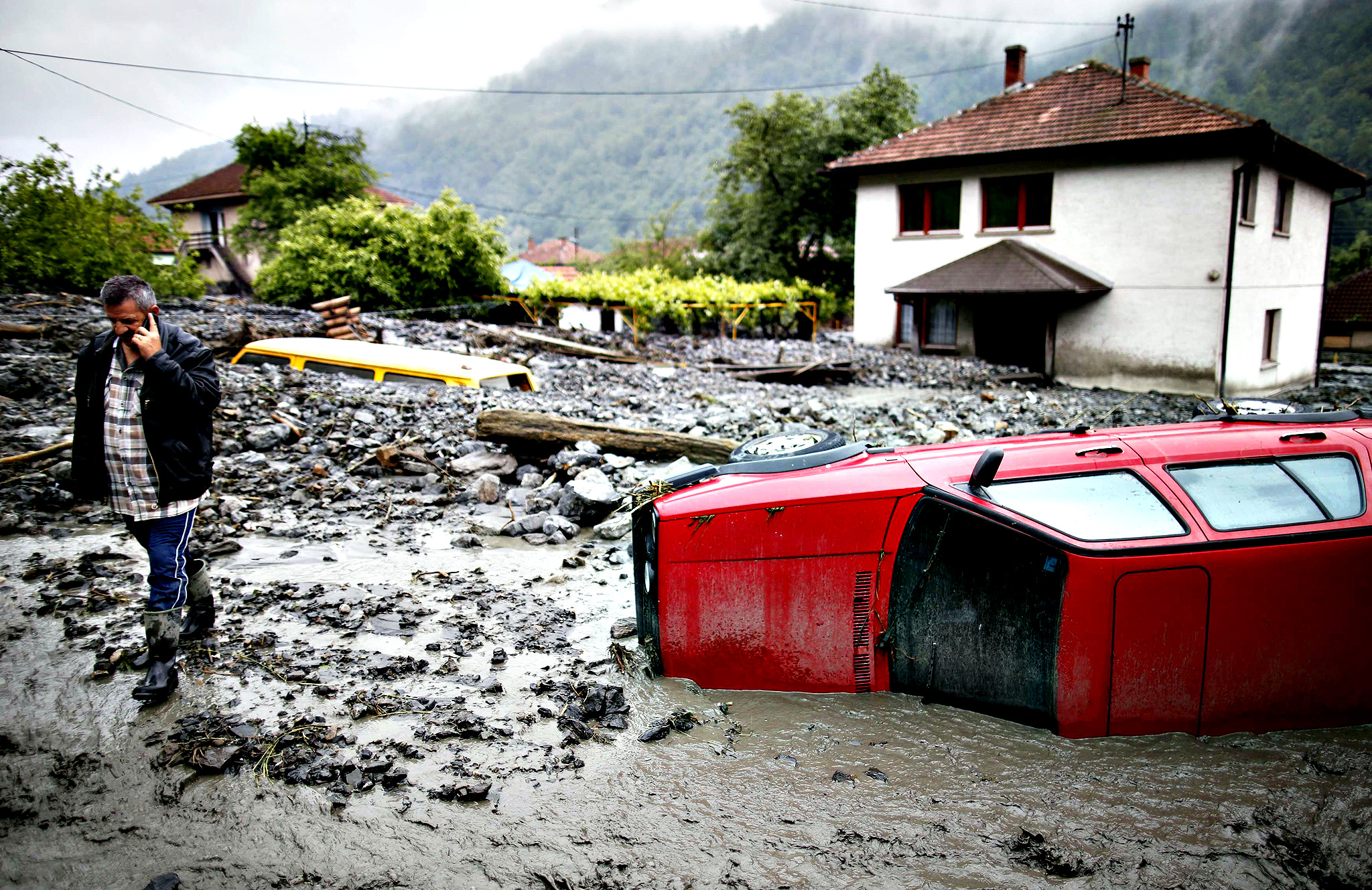 Asim Skopljak talks on a mobile phone as he walks near a car stranded in mud on a street that was hit by floods in Topcic Polje, near Zepce May 16, 2014. The heaviest rains and floods in 120 years have hit Bosnia and Serbia, killing five people, forcing hundreds out of their homes and cutting off entire towns.
