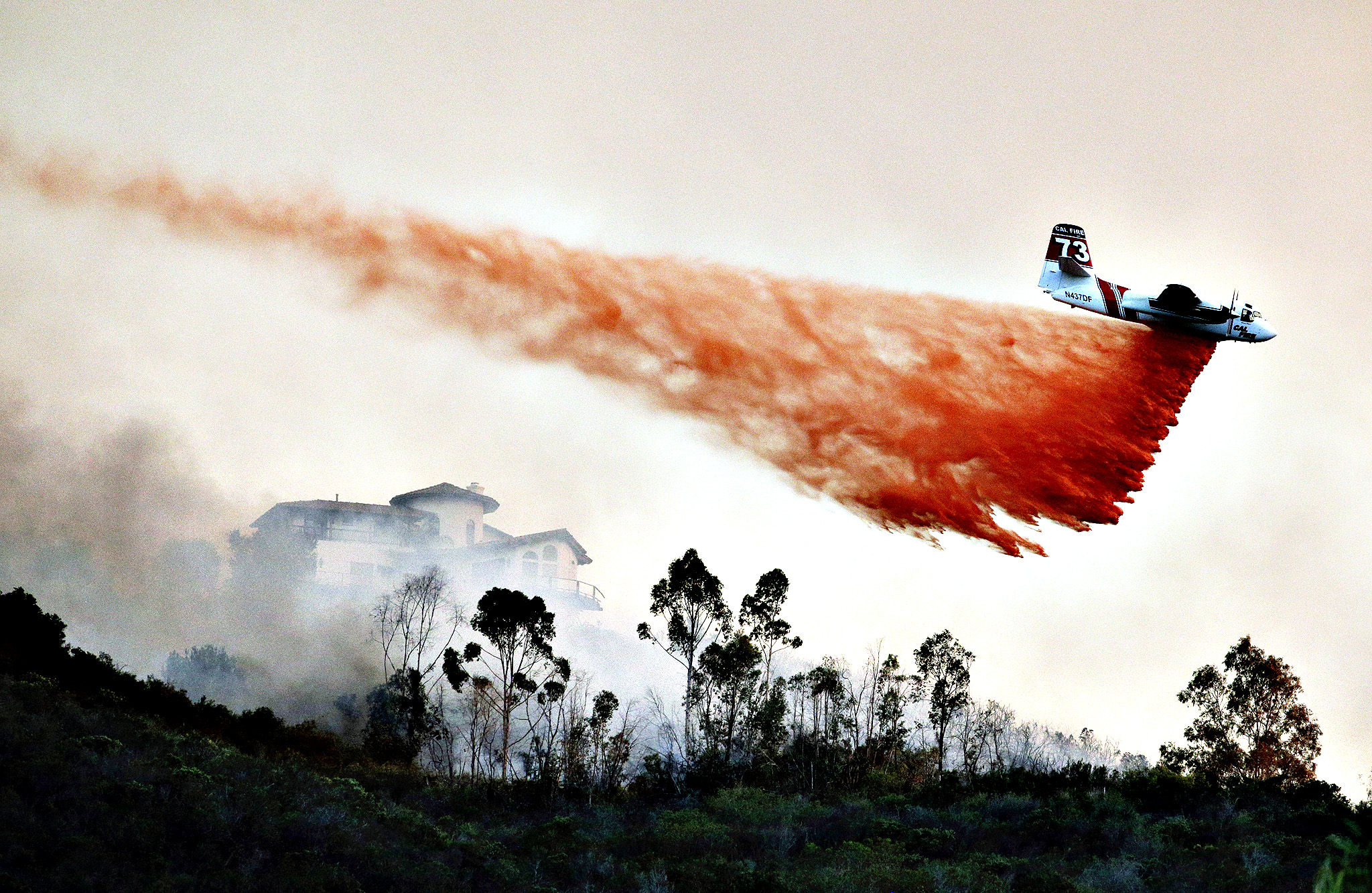 A plane drops fire retardant over a hot spot on Wednesday, May 14, 2014, in San Marcos, Calif. Wednesday, May 14, 2014, in San Marcos, Calif. Flames engulfed suburban homes and shot up along canyon ridges in one of the worst of several blazes that broke out Wednesday in Southern California during a second day of a sweltering heat wave, taxing fire crews who fear the scattered fires mark only the beginning of a long wildfire season.