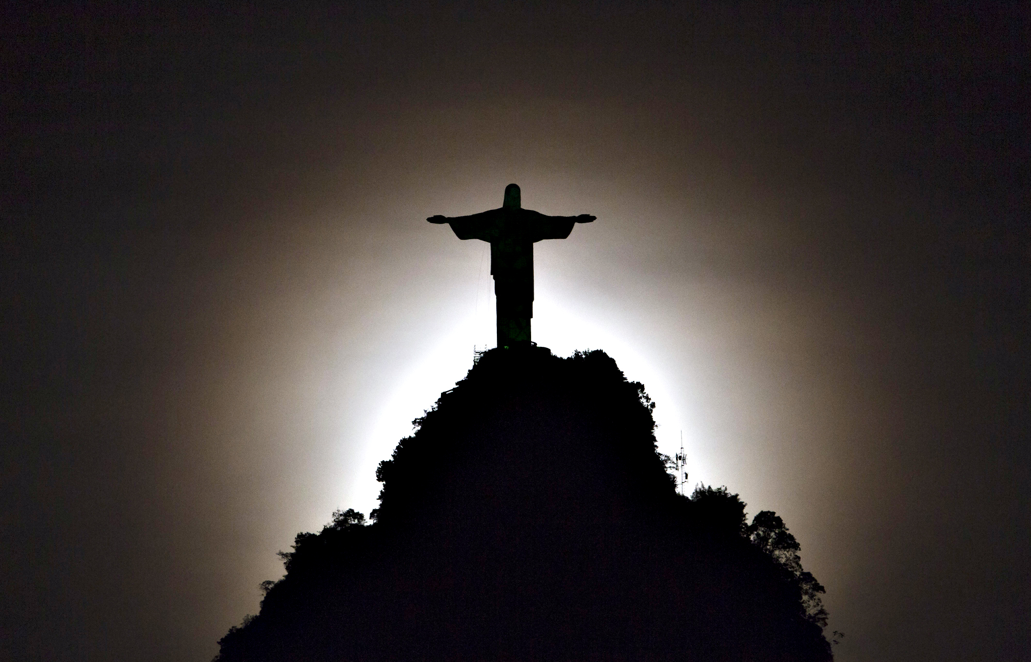 Christ the Redeemer statue is silhouetted against the glow of the moonset in Rio de Janeiro, Brazil, Tuesday, May 13, 2014.  As opening day for the World Cup approaches, people continue to stage protests, some about the billions of dollars spent on the World Cup at a time of social hardship, but soccer is still a unifying force. The international soccer tournament will be the first in the South American nation since 1950.