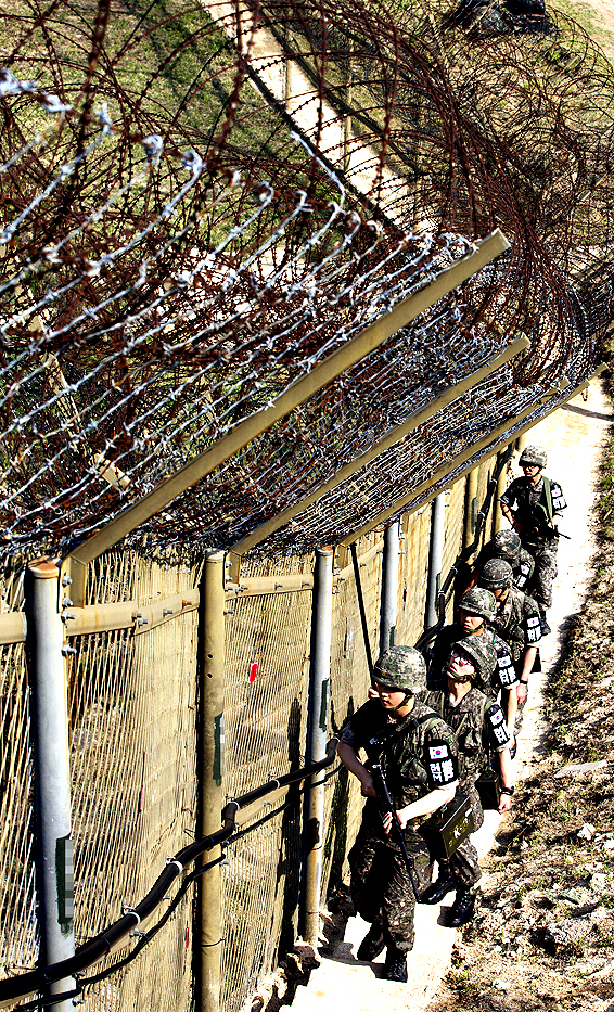 "South Korean army soldiers patrol along the barbed-wire fence at the demilitarized zone (DMZ) in Cheorwon, South Korea, Tuesday, May 13, 2014. North Korea warned Tuesday that a South Korean official would pay a high price for saying the North ""must disappear soon"" in an escalation of rhetoric between the rivals."