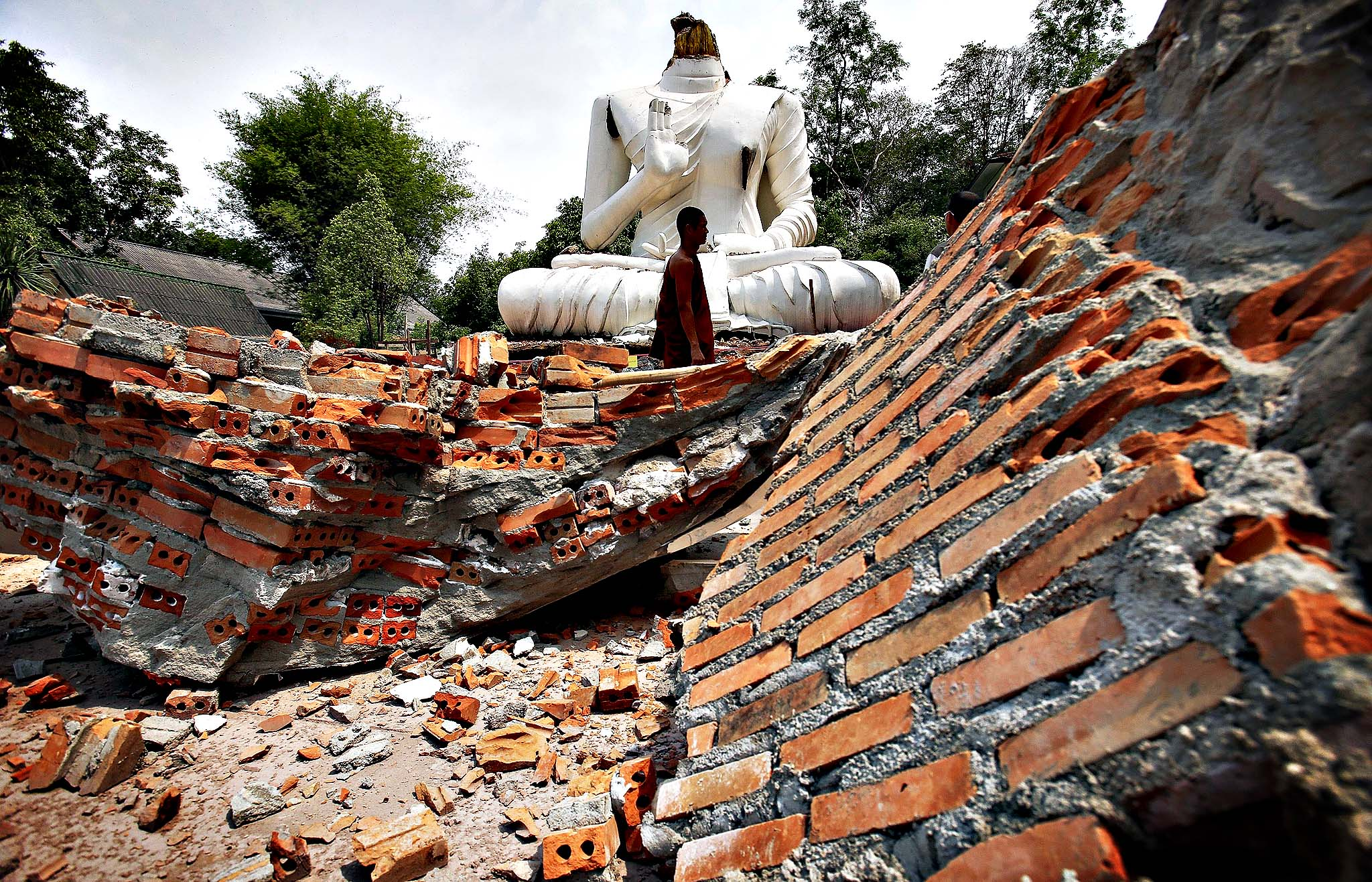 A Buddhist monk walks in front of a Buddha statue damaged in the earthquake at the Udomwaree temple in Chiang Rai, in northern Thailand...A Buddhist monk walks in front of a Buddha statue damaged in the earthquake at the Udomwaree temple in Chiang Rai, in northern Thailand May 6, 2014. An earthquake of 6 magnitude struck northern Thailand on Monday causing some damage to buildings and roads and knocking goods off shelves in shops but there were no immediate reports of any casualties.