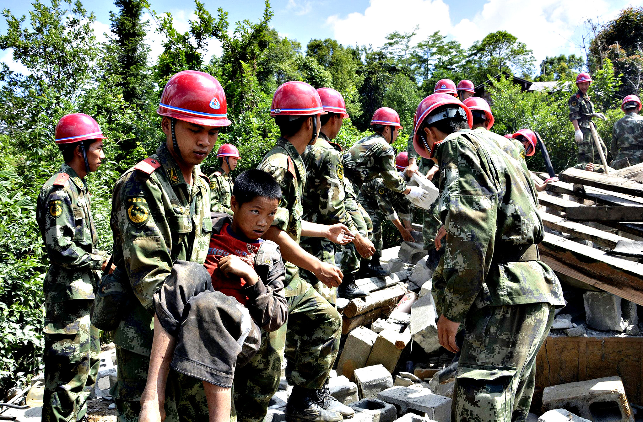 Paramilitary policemen carry out an injured boy after a 6.1 magnitude earthquake hit Yingjiang county, Yunan province. According to local media, at least 34 people were injured in the earthquake on Friday morning.