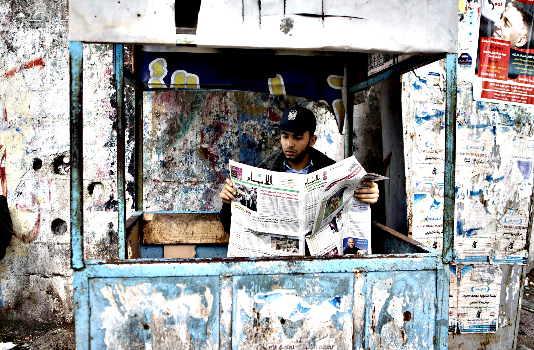 A Palestinian Hamas policeman reads a copy of the Al-Ayyam newspaper in Gaza City, on May 8, 2014. The Palestinian daily which is edited and printed in the West Bank city of Ramallah has been allowed by the Hamas to be distributed in the Gaza strip for the first time in seven years, after the Islamist movement and the western-backed Palestinian Authority signed a surprise reconciliation agreement on April 23 in a bid to end years of bitter and sometime bloody rivalry.