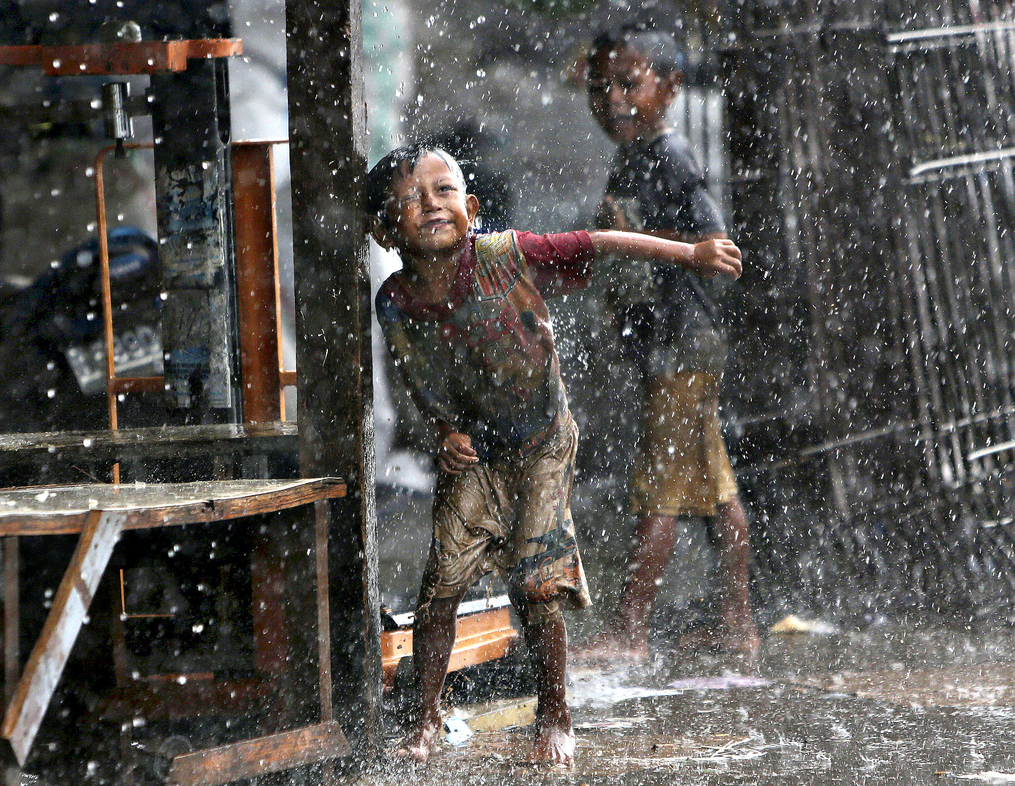 Indonesian children play in the rain during a heavy downpour in Jakarta, Indonesia