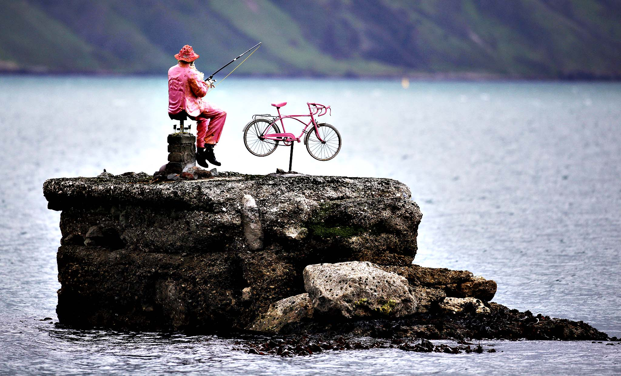 A pink statue of a man fishing next to his bike sits on the rocks at Waterfoot, Northern Ireland, Tuesday, May, 6, 2014, in preparation for the Giro d'Italia. Many towns and villages across Ireland have been going pink in preparation for the Giro d'Italia which has three stages in Ireland running from May 9-11.