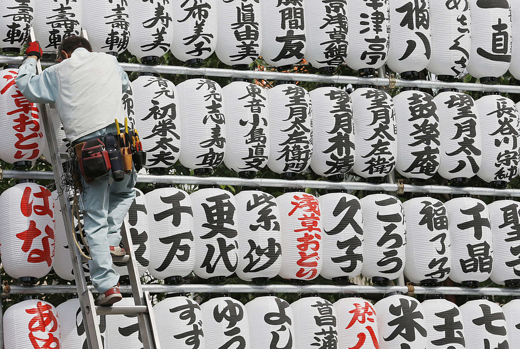 A worker goes down a ladder after adjusting a display of paper lanterns at Sensoji temple at Asakusa traditional shopping district in Tokyo, Monday, May 19, 2014. The lanterns carry the names of Buddhist temple parishioners and other supporters who donated money to the temple. (AP Photo/Shizuo Kambayashi)