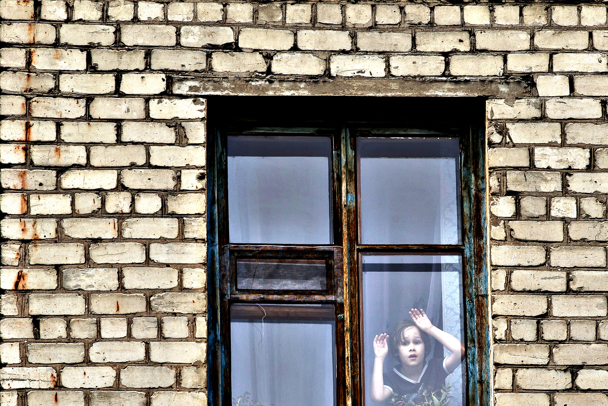 A child leans against a window as he looks at Ukrainian miners marching in support of the Donetsk People's Republic in Lenin square, Donetsk, Ukraine, Wednesday, May 28, 2014. Miners who, according to local media, have declared an open ended strike, protested against recent actions by Ukraine's military against rebels who tried to take control of the Donetsk airport Monday but were repelled by Ukrainian forces using combat jets and helicopter gunships in clashes that killed up to 100 rebel fighters. Banner reads Fascists will not pass in reference to the Ukrainian government forces.