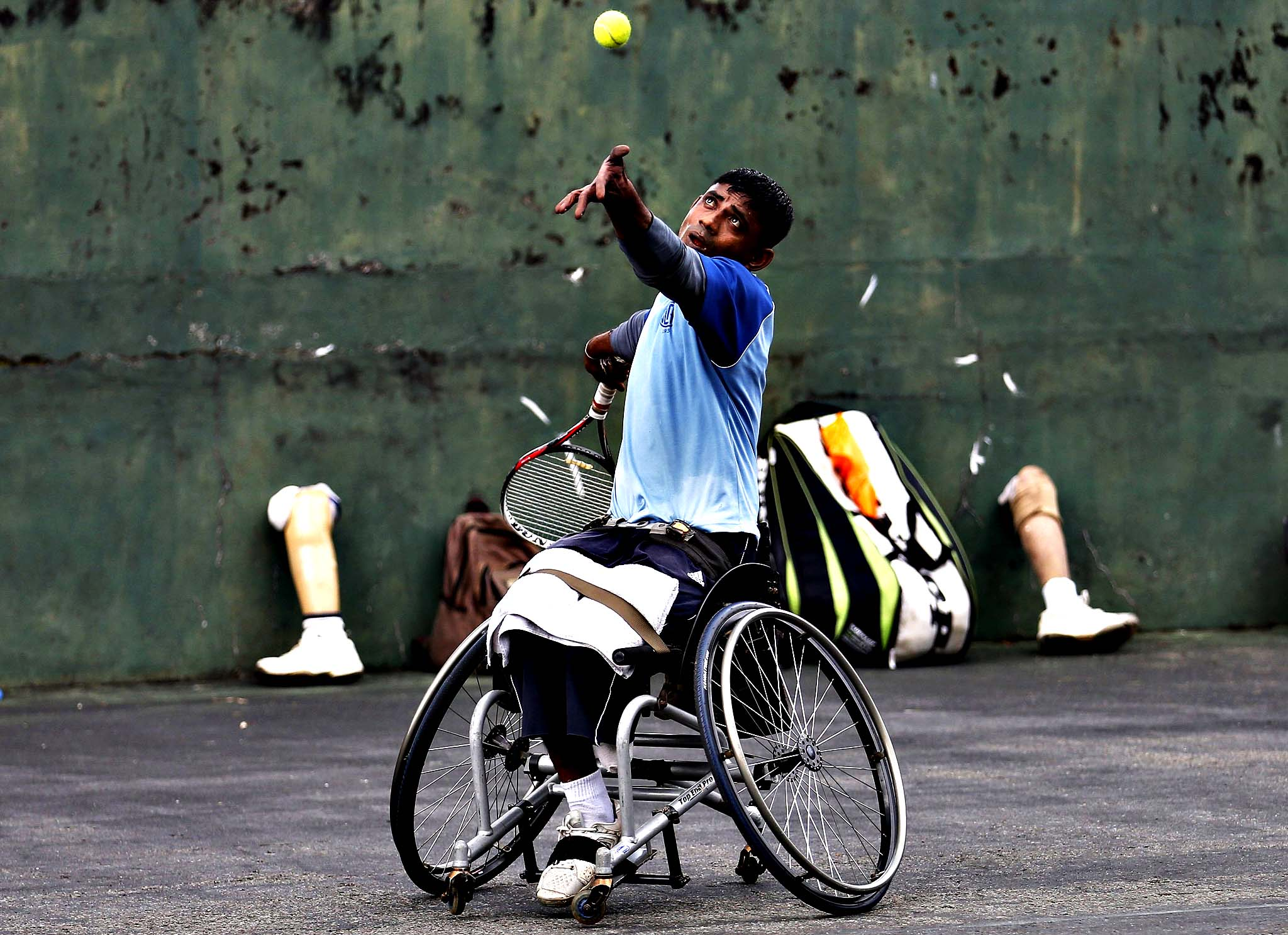 Gamini Dissanayake, 36, an army soldier and member of Sri Lanka's wheelchair tennis national team serves during a practice session in Colombo May 6, 2014. The Sri Lankan national wheelchair team is made up of active armed forces members who lost their limbs during active duty.