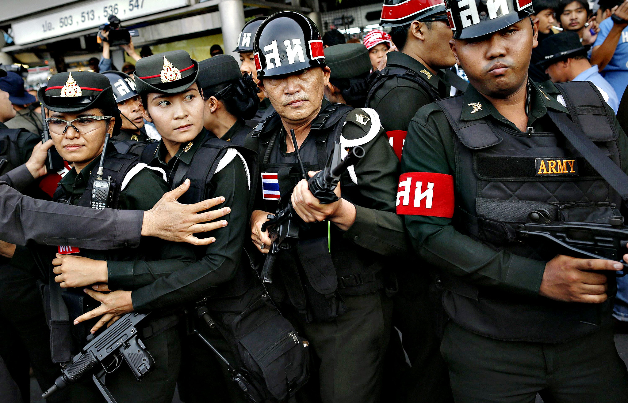 "Military policemen hold their weapons as they are surrounded by a mob during a confrontation between anti-coup protesters and military at the Victory monument in Bangkok...Military policemen hold their weapons as they are surrounded by a mob during a confrontation between anti-coup protesters and military at the Victory monument in Bangkok May 28, 2014. There have been daily protests in Bangkok against the coup and on Wednesday about 200 people confronted troops and police at the Victory Monument. Protesters jeered and threw plastic water bottles and spray-painted ""Get Out"" and ""No Coup"" over an army Humvee."