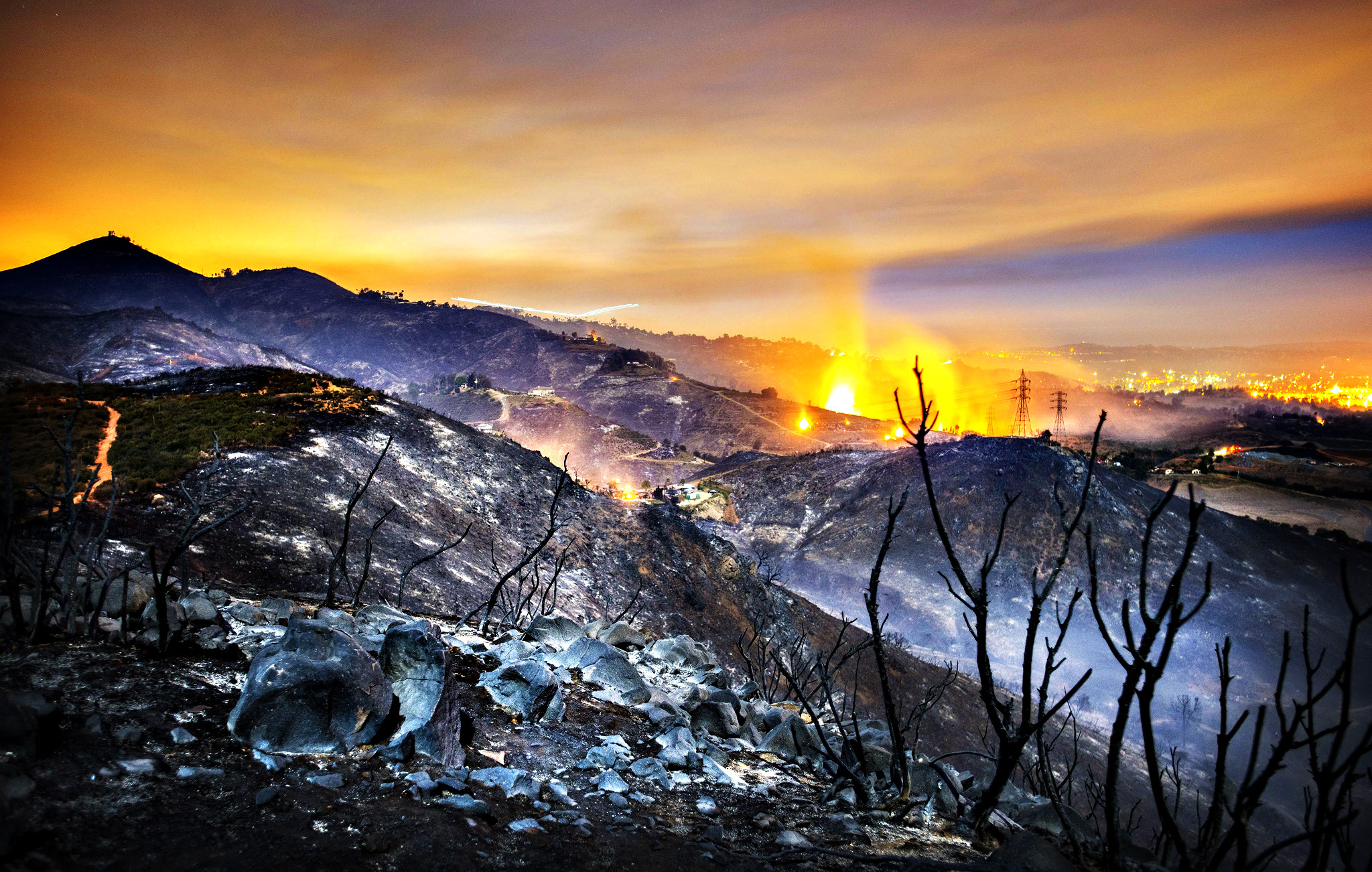 A longtime exposure shows smolderings remains of overnight fires on the hillsides of San Marcos, San Diego county, California, USA, early 16 May 2014. Over 1,000 firefighters battled a series of fast-moving southern California wildfires on 15 May that spread across the region despite the efforts of more than 20 firefighting aircraft. Huge clouds of black smoke hung over much of San Diego County, where the worst blazes were burning 15 May, driven by the blistering Santa Ana winds, which bring strong, dry gusts out from the interior desert.