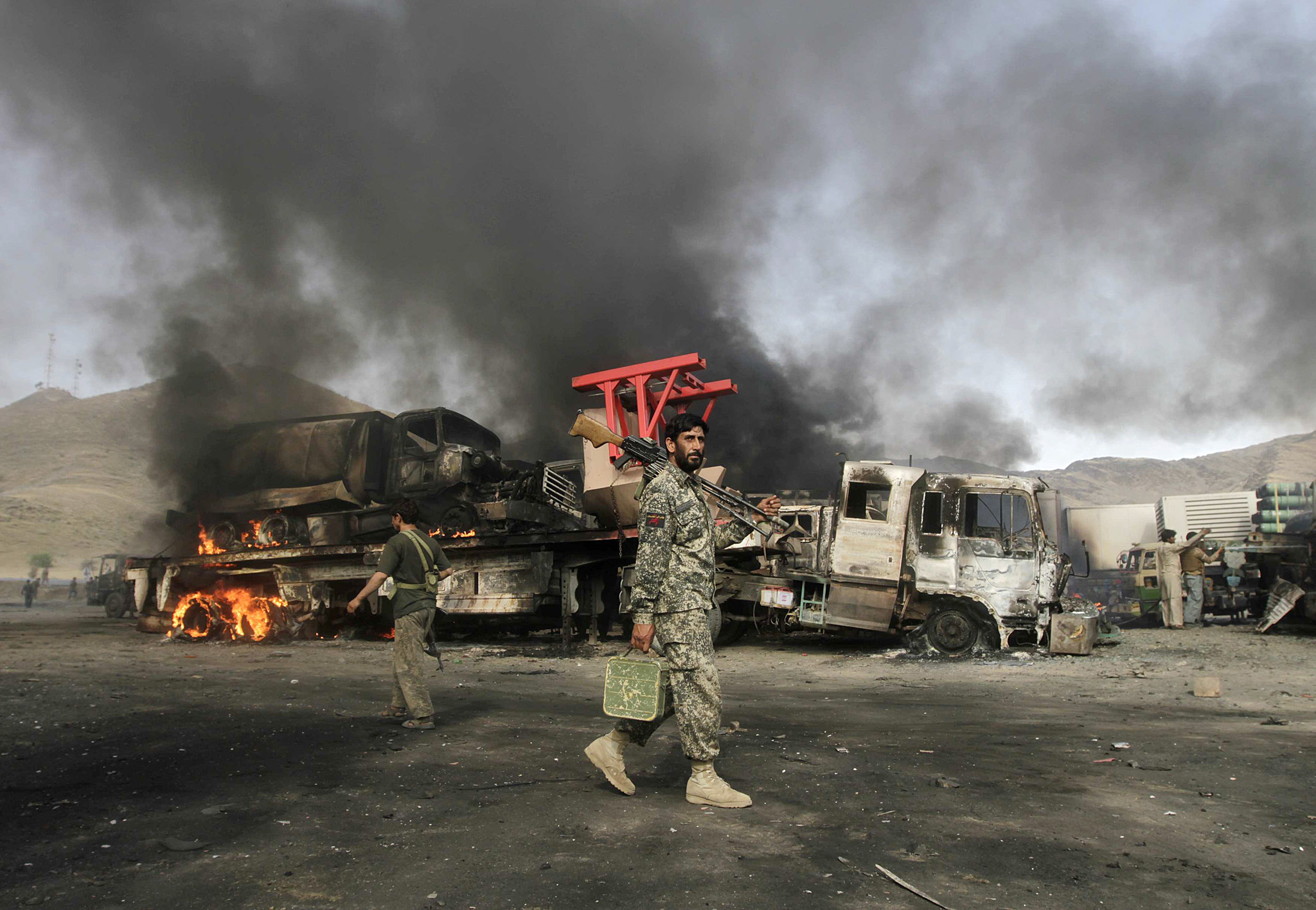 Afghan security forces walk near burning NATO supply trucks after, what police officials say, was an attack by militants in the Torkham area...Afghan security forces walk near burning NATO supply trucks after, what police officials say, was an attack by militants in the Torkham area near the Pakistani-Afghan in Nangarhar Province June 19, 2014. According to officials on Thursday, at least 37 trucks belonging to NATO forces were destroyed after three suicide bombers targeted the NATO supply trucks, with two civilians wounded in the attack.   REUTERS/Parwiz (AFGHANISTAN - Tags: CIVIL UNREST POLITICS)