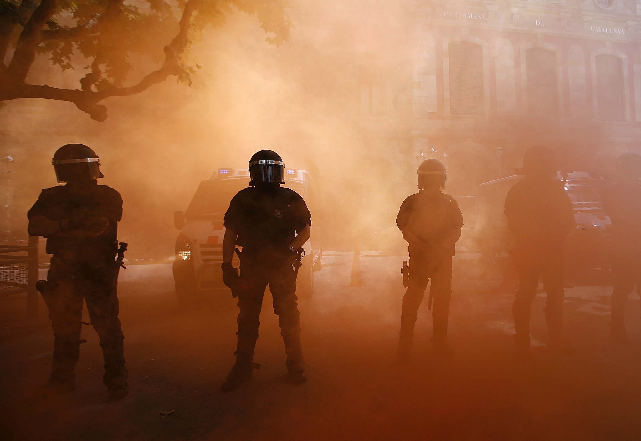 Riot police stand among red smoke during protest by a firemen against budgets cuts next to Catalunya's Parliament in Barcelona...Riot police stand among red smoke during protest by a firemen against budgets cuts next to Catalunya's Parliament in Barcelona June 10, 2014. REUTERS/Albert Gea
