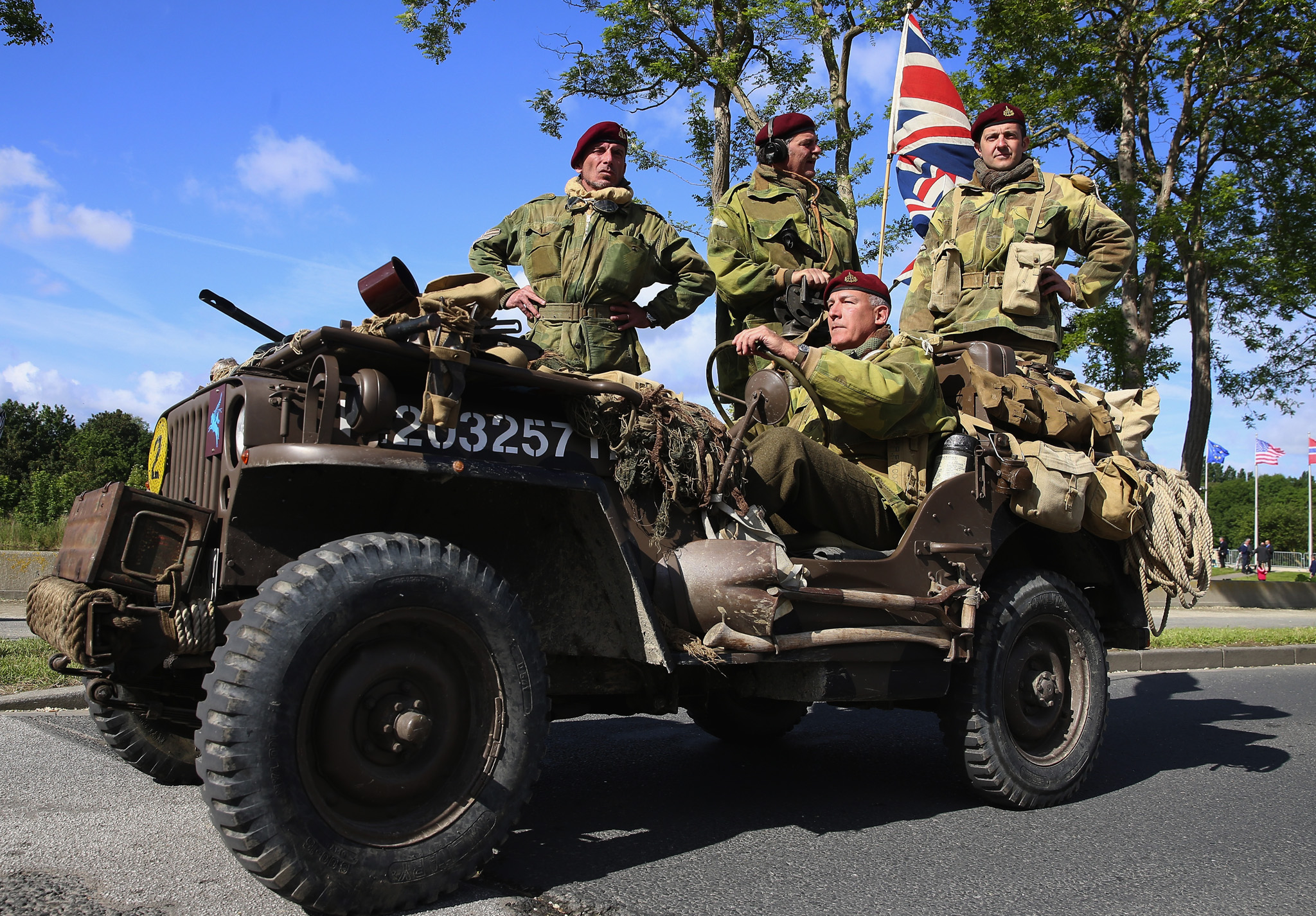 The 70th Anniversary Of The D-Day Landings Are Commemorated In Normandy...RANVILLE, FRANCE - JUNE 05:  Soldiers travelling on a vintage jeep cross Pegasus Bridge (also known as the BÈnouville Bridge) during D-Day Commemorations on June 5, 2014 in Ranville, France. Friday 6th June is the 70th anniversary of the D-Day landings which saw 156,000 troops from the allied countries including the United Kingdom and the United States join forces to launch an audacious attack on the beaches of Normandy,  these assaults are credited with the eventual defeat of Nazi Germany. A series of events commemorating the 70th anniversary are planned for the week with many heads of state travelling to the famous beaches to pay their respects to those who lost their lives.  (Photo by Chris Jackson/Getty Images)
