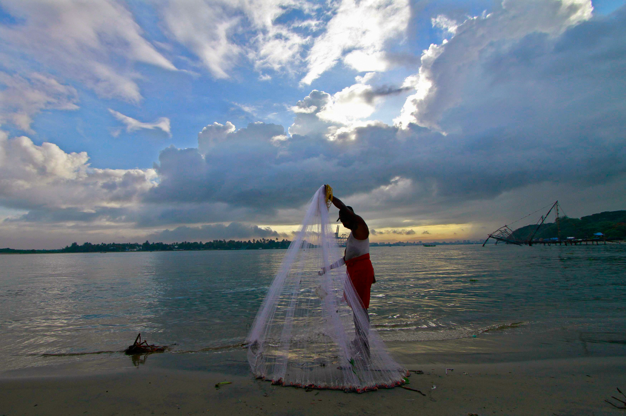 A fisherman arranges his fishing net at a beach against the backdrop of pre-monsoon clouds in Kochi...A fisherman arranges his fishing net at a beach against the backdrop of pre-monsoon clouds in the southern Indian city of Kochi June 5, 2014. India's southern coast could witness the arrival of this year's monsoon in the next day or so after sporadic rains in recent days heralded the arrival of the wet season that is crucial to farmers in Asia's third-largest economy. REUTERS/Sivaram V. (INDIA - Tags: AGRICULTURE ENVIRONMENT BUSINESS)